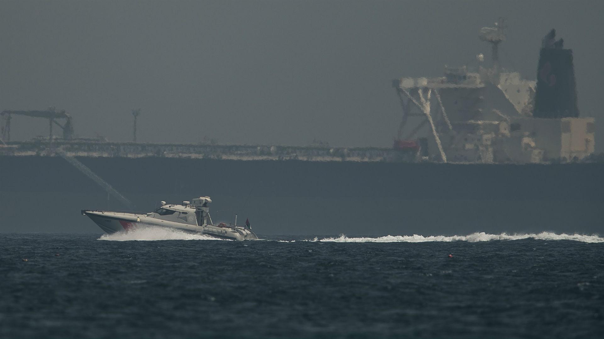 Un navío de la Guardia Costera emiratí pasa junto a un petrolero frente a la costa de Fujairah, Emiratos Árabes Unidos, el lunes 13 de mayo de 2019. (AP Foto/Jon Gambrell)
