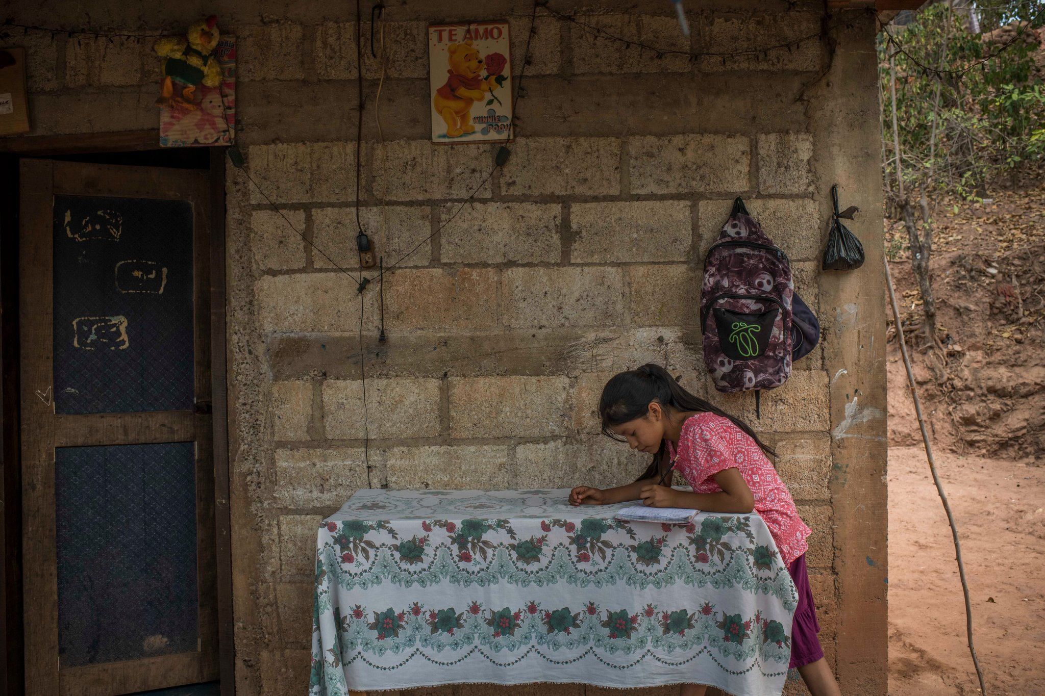Gabriela Pablo hace la tarea, en el patio de su casa. (Daniele Volpe para The New York Times)