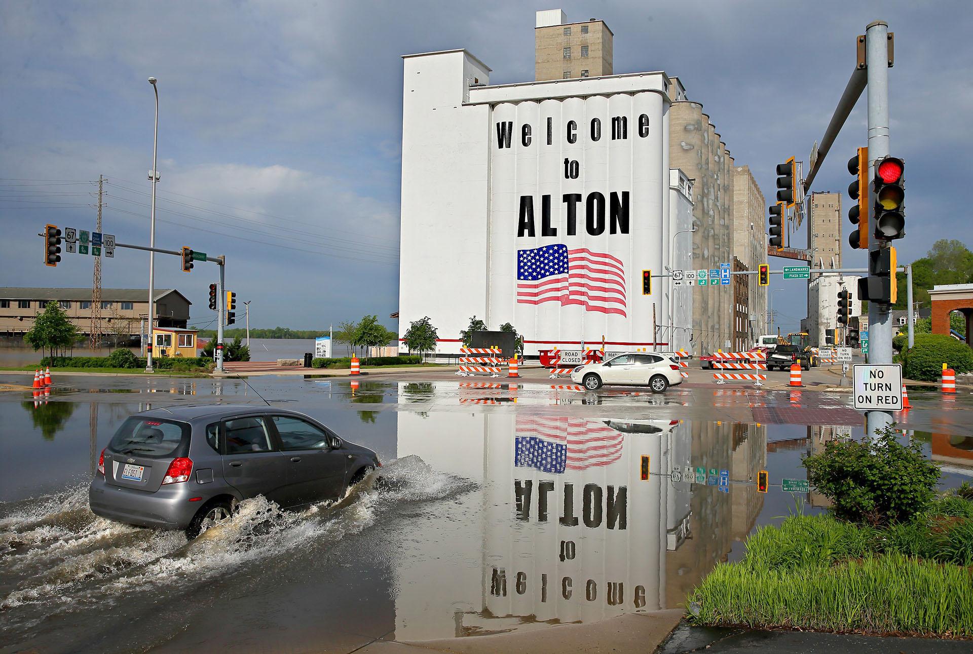 """Un vehículo pasa por las aguas de la inundación del río Misisipi en el centro de Alton, Illinois, el lunes 6 de mayo de 2019. """"Apenas estamos manteniendo la cabeza por encima del agua"""", dijo Brent Walker, el alcalde la ciudad. (AP)"""