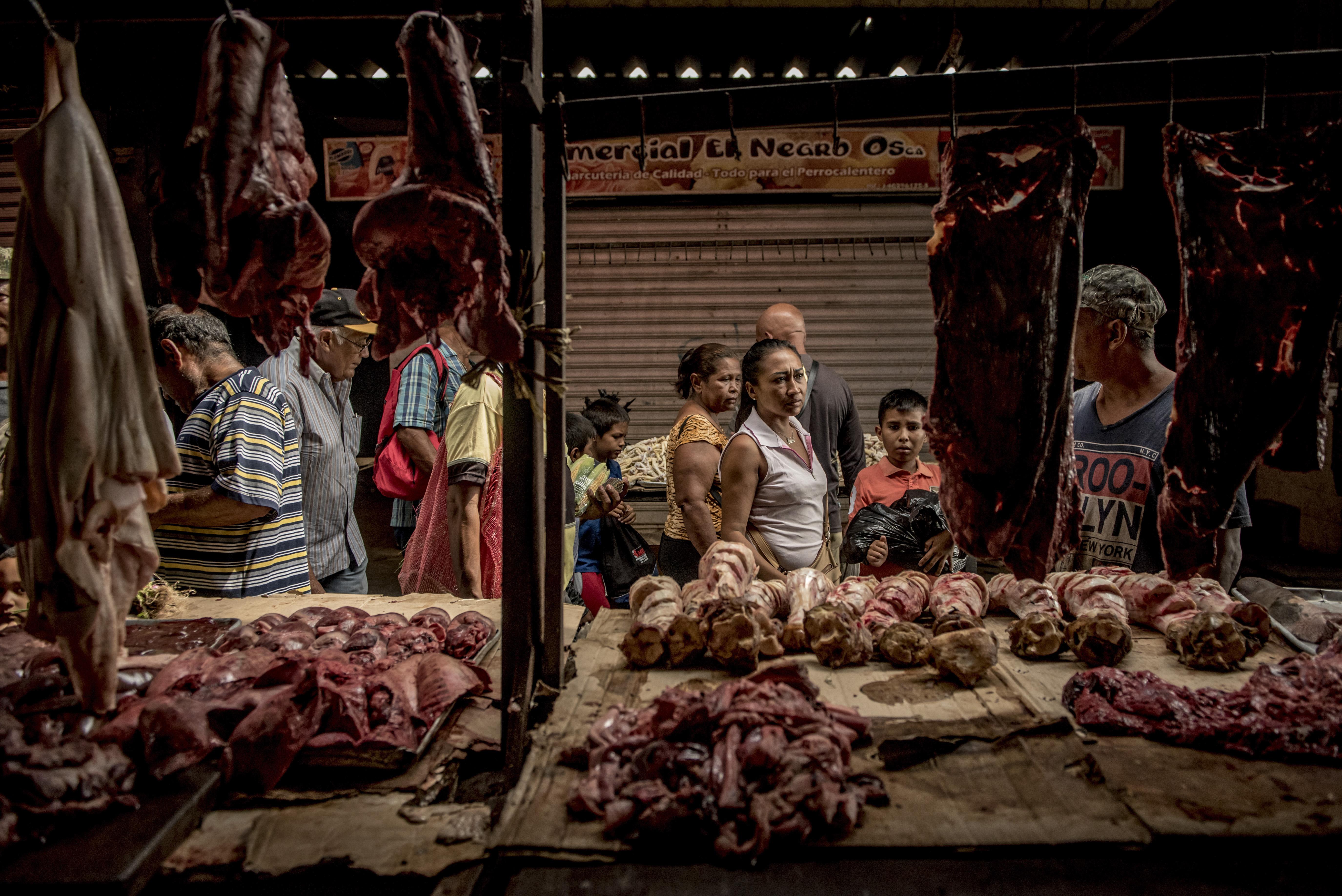 Personas que compraban despojos no refrigerados y otros subproductos de carne de res en un mercado de Maracaibo. (Meridith Kohut/The New York Times)