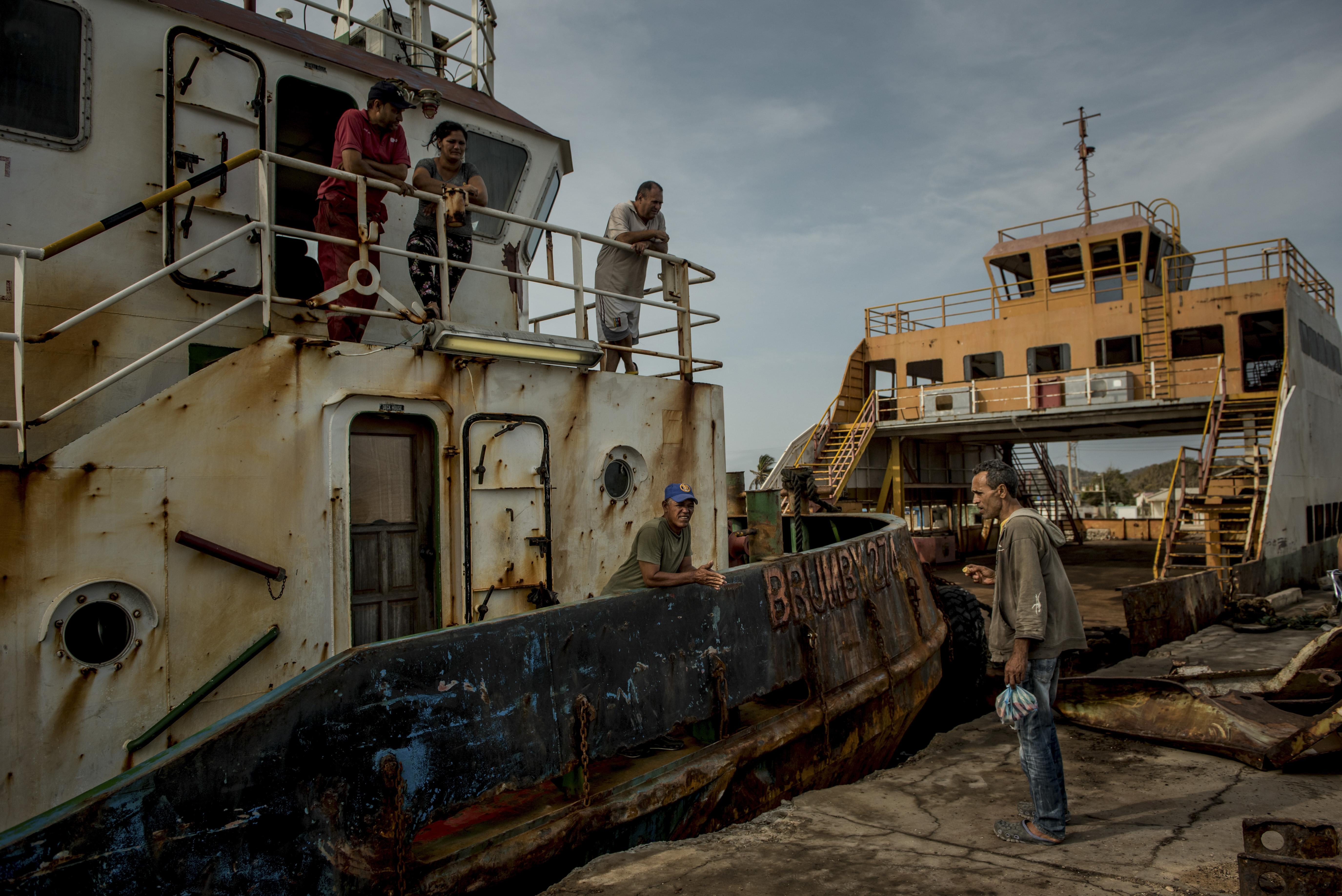 Un barco petrolero arrastra el ferry oxidado desde la Isla de Toas hacia el continente para conseguir escasas cantidades de alimentos subsidiados. . (Meridith Kohut/The New York Times)