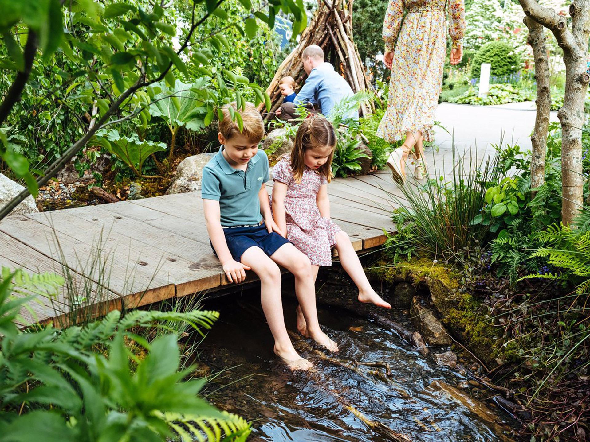 El príncipe George y su hermana, la princesa Charlotte, se relajan en la pasarela de madera. De fondo se puede ver al príncipe William con Louis