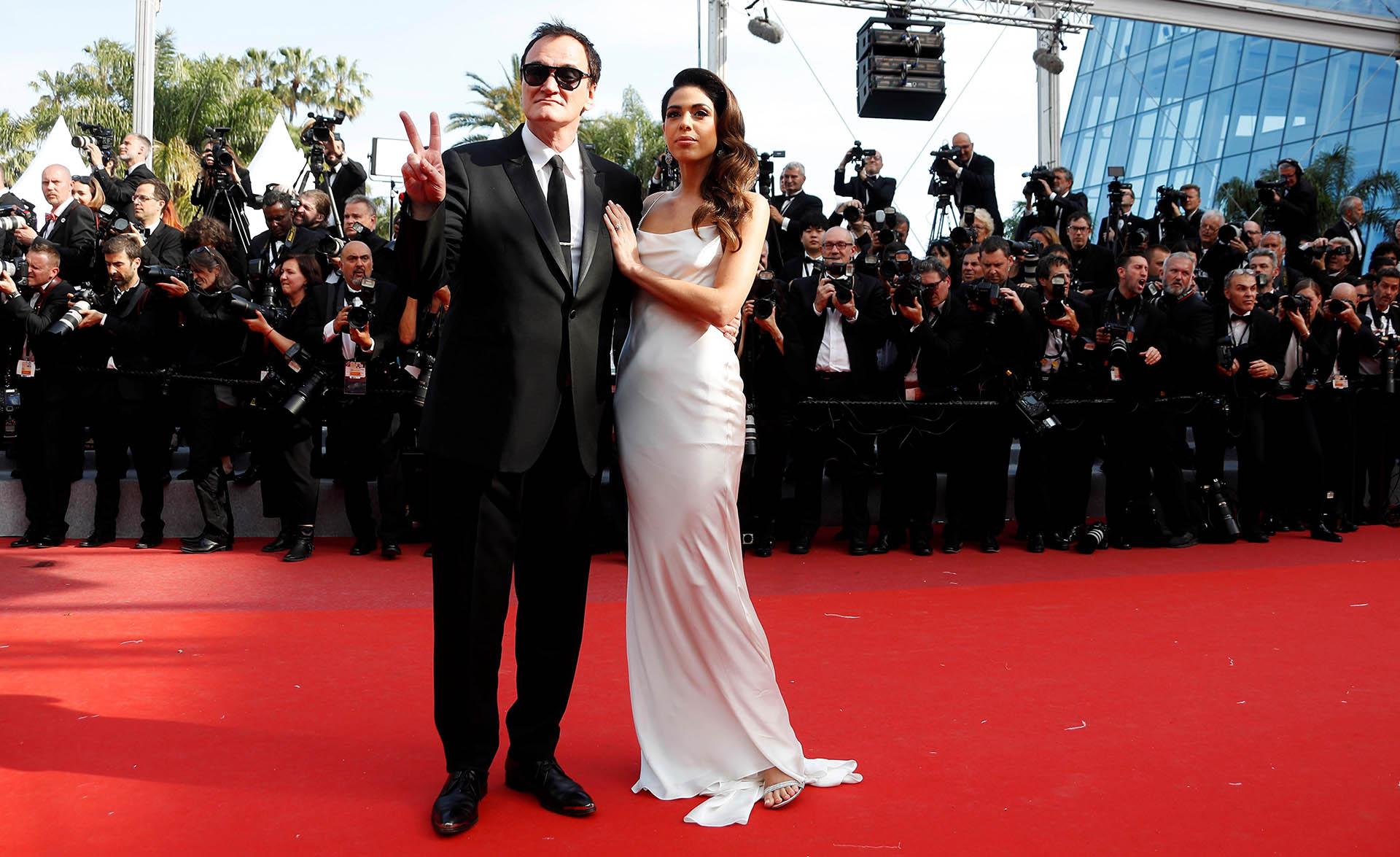 Quentin Tarantino y su mujer Daniella Pick. Él apostó a un black tie con corbata slim y ella un vestido blanco con sandalias. Con un beauty look de costado, impactó en la red carpet de Cannes