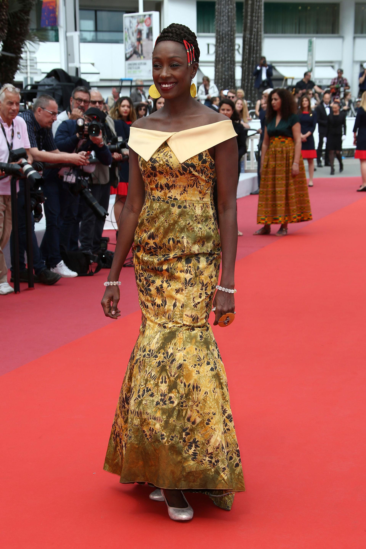 Maimouna N'Diaye no lució un adecuado atuendo para estar a la altura de la red carpet de Cannes. Apostó a un vestido sirena en dorado estampado con escote off shoulders y completó el look con dos pulseras de cuentas transparentes y un maxi anillo