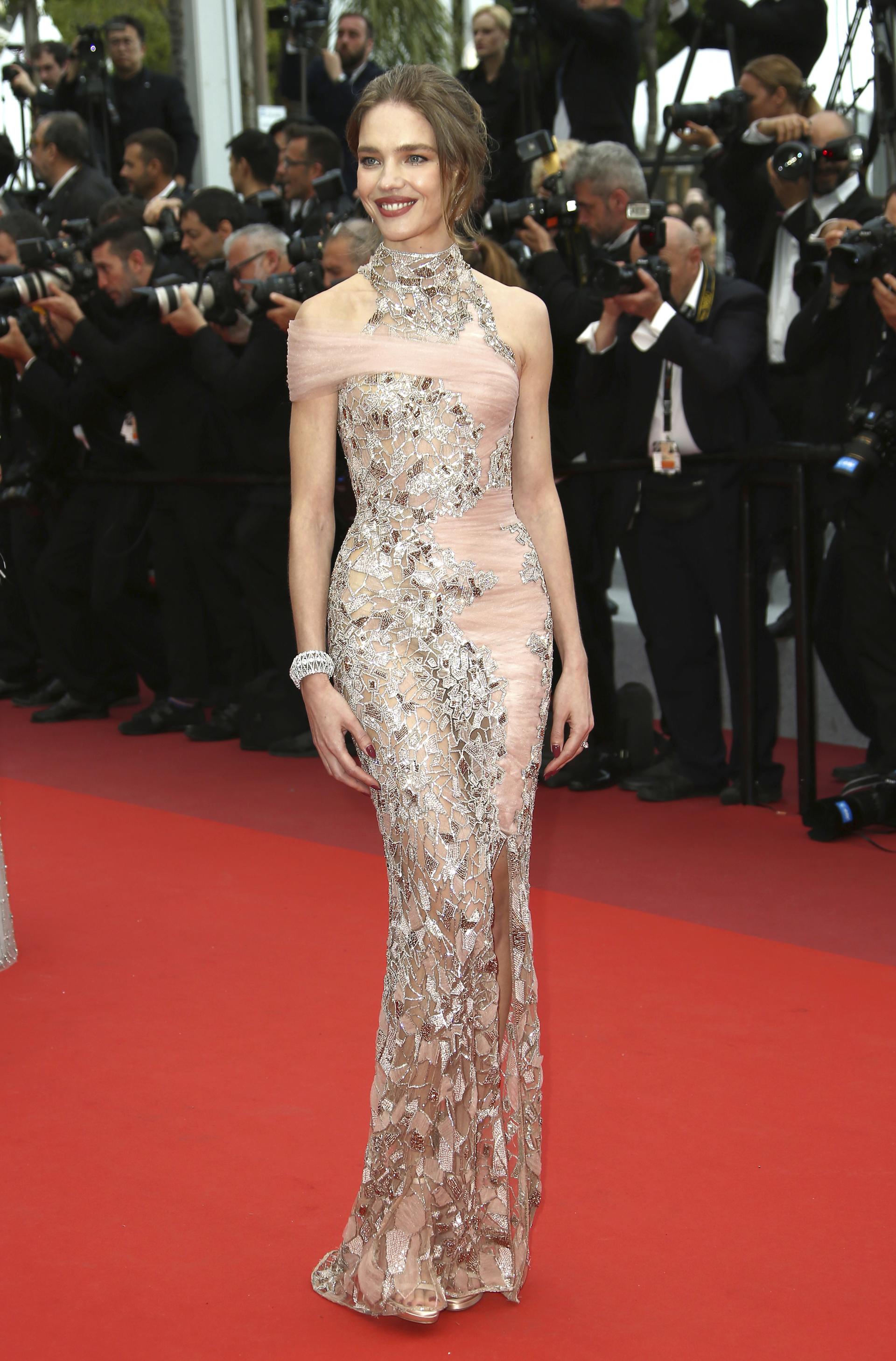 Natalia Vodianova lució un diseño traslúcido con cuello halter y drapeado con detalles de apliques de espejos en todo el vestido.Como accesorio, brazalete de brillantes, y beauty look con boca bordó y peinado semi recogido