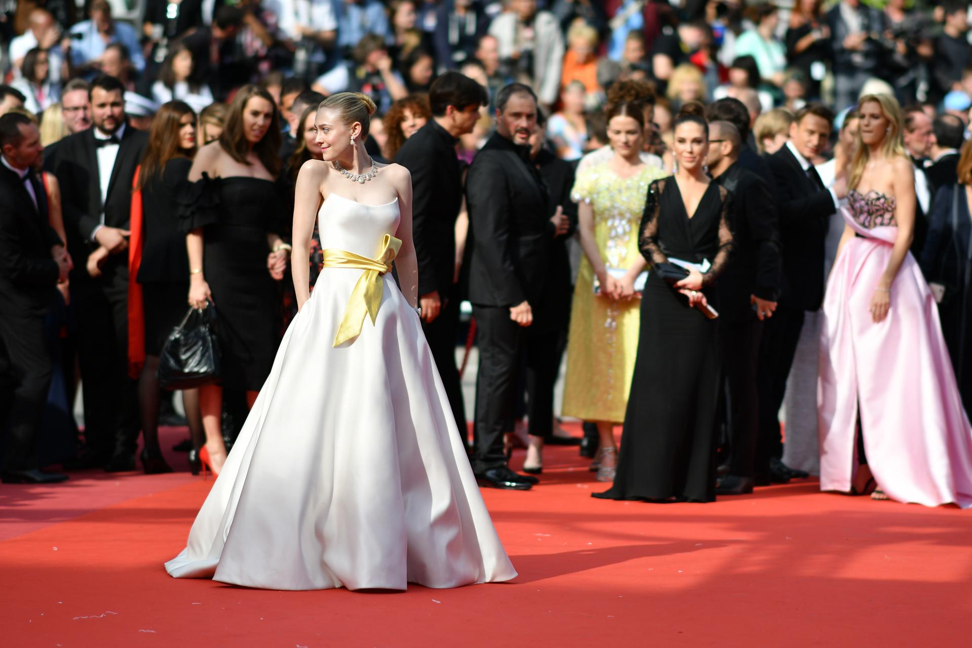 Dakota Fanning lució un diseño strapless con lazo amarillo. Completó su look con gargantilla de cristales y pequeños aros colgante