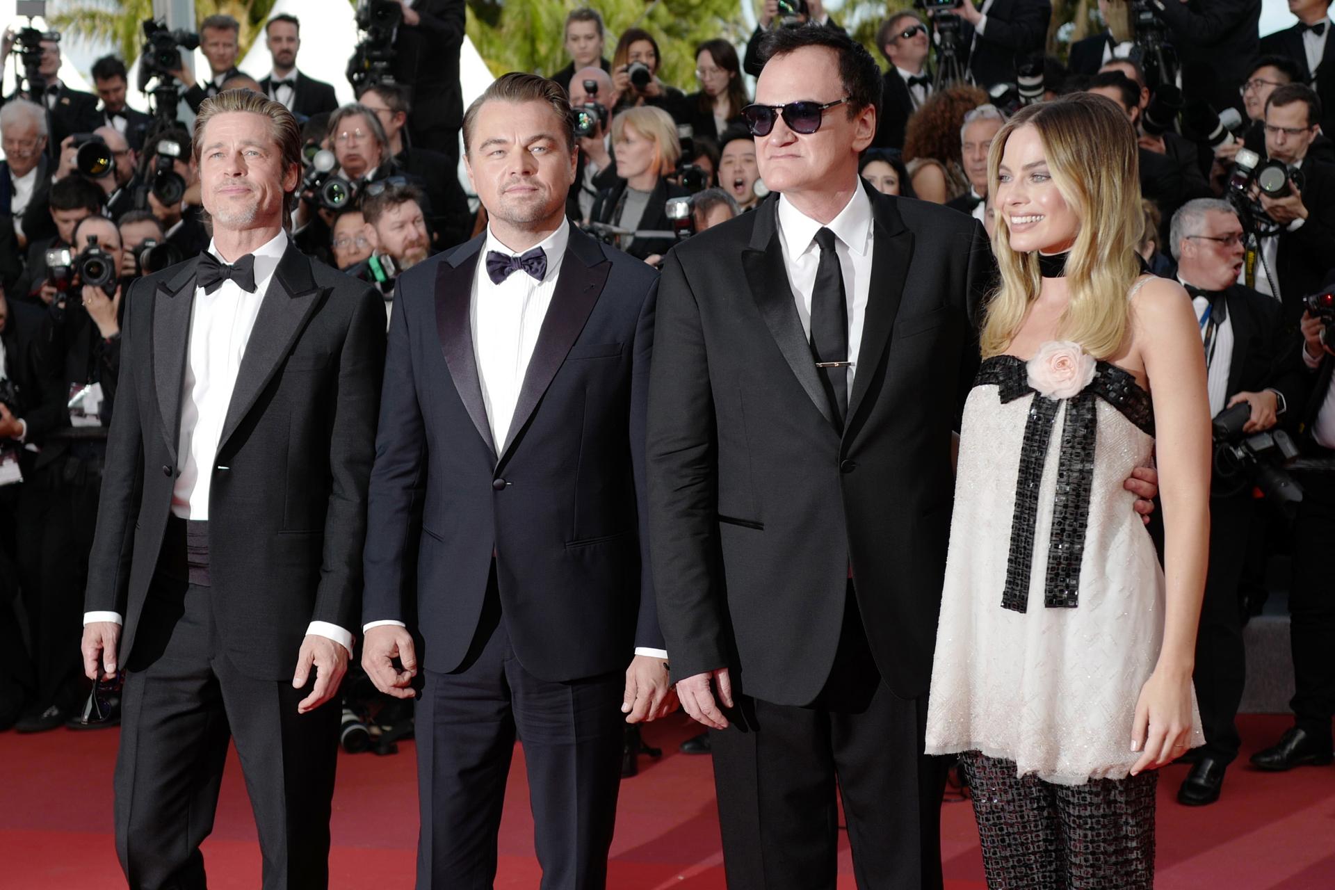 Brad Pitt, Leonardo DiCaprio con black tie de moño Quentin Tarantino y black tie de corbata y Margot Robbie con vestido corto y pantalón de lentejuelas con detalle de rosa rosada en el borde del vestido. Como accesorio, una gargantilla de chiffón