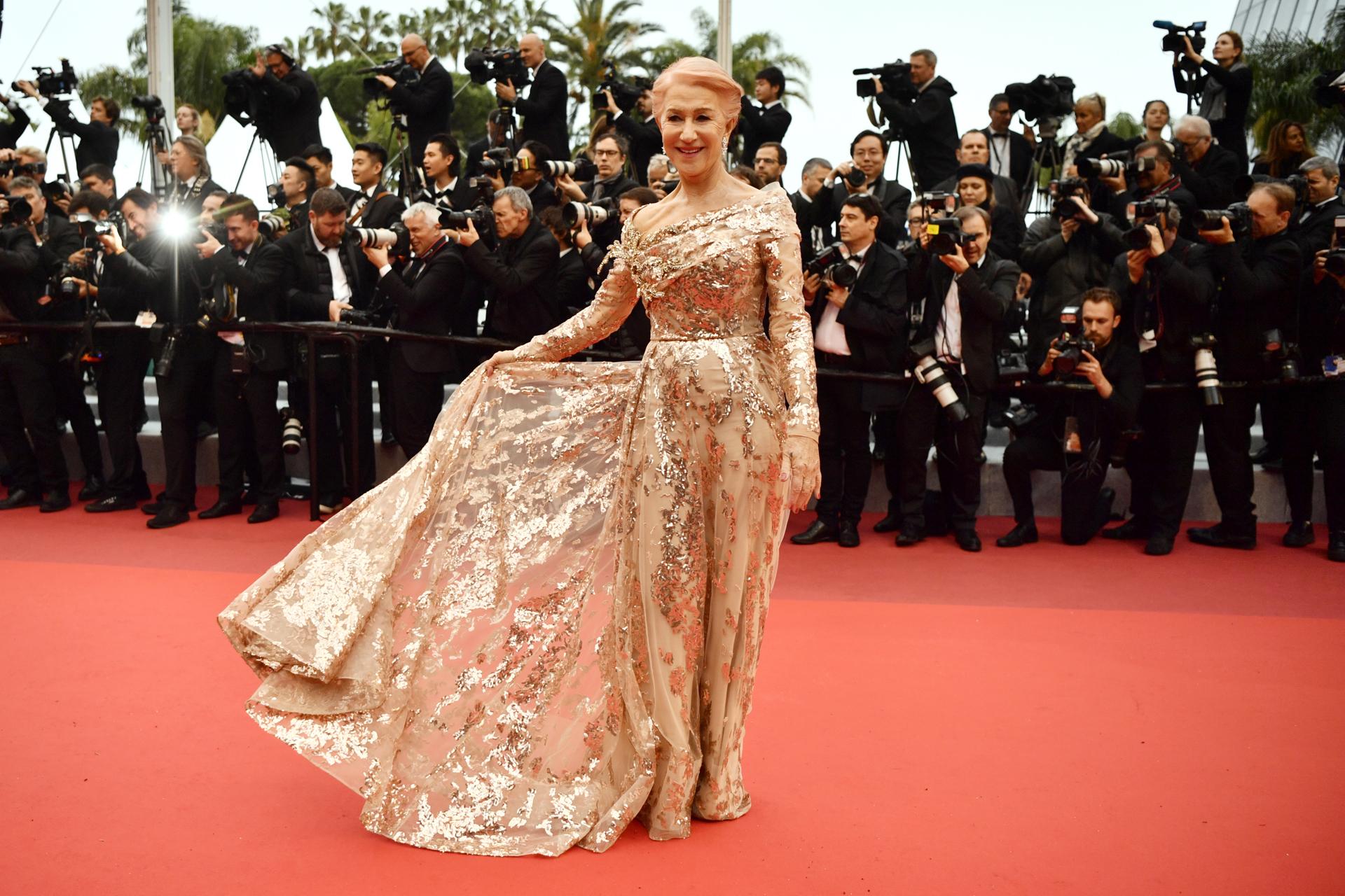 Helen Mirren eligió un vestido dorado de corte asimétrico en su escote, con mangas largas y sobrefalda. Sin accesorios, el bordado