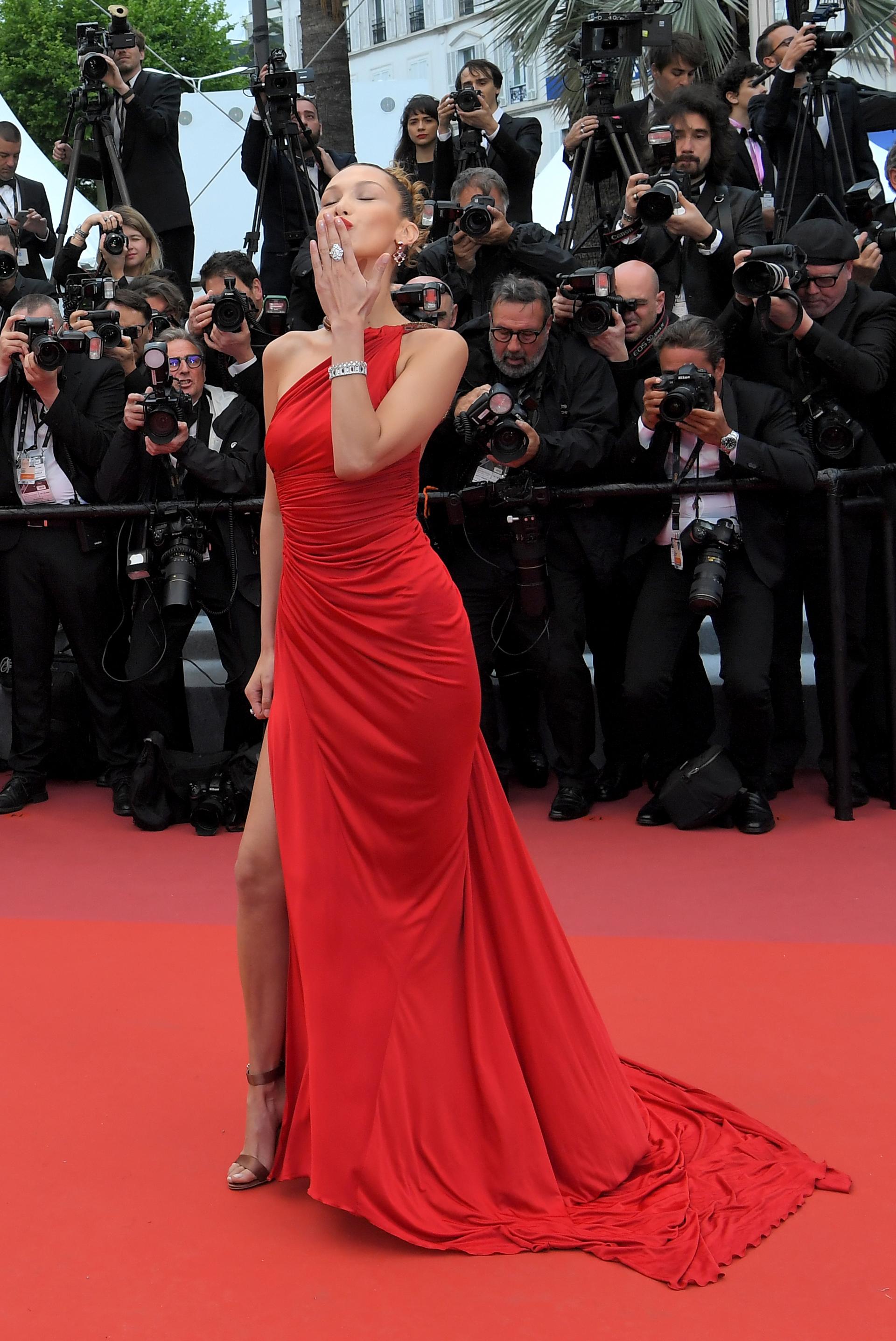Bella Hadid, una de las invitadas a la red carpet de Cannes lució un vestido rojo de lycra, drapeado súper tajo y cuello halter. Completó el look con joyas de brillantes, anillos, brazaletes y aros gota