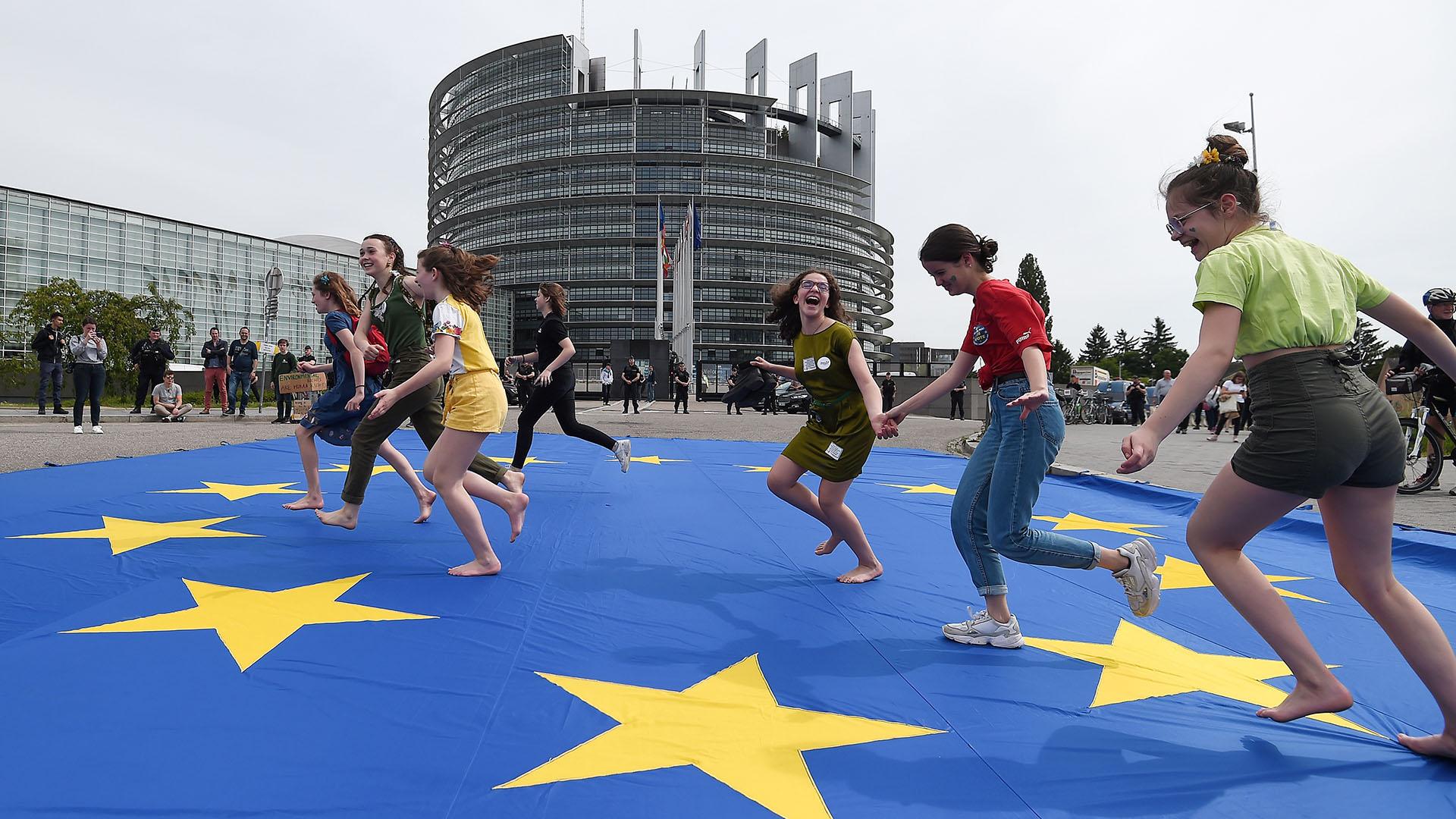 Jóvenes corren sobre una bandera europea gigante mientras participan en una protesta exigiendo acción urgente contra el calentamiento global, el 24 de mayo de 2019, ante el Parlamento Europeo en Estrasburgo, al este de Francia. (AFP)