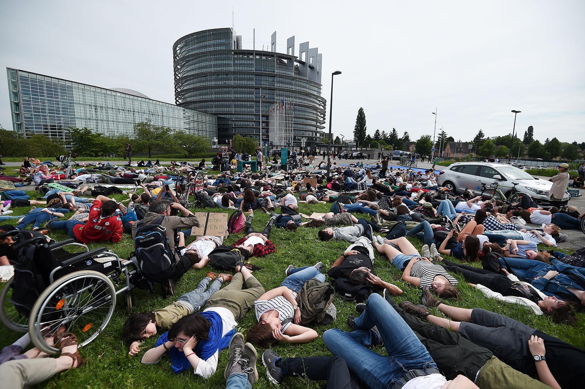 Jóvenes anticipan las consecuencias del cambio climático haciéndose los muertos durante una protesta que exige una acción urgente contra el calentamiento global, el 24 de mayo de 2019, ante el Parlamento Europeo en Estrasburgo, en el este de Francia. (AFP)