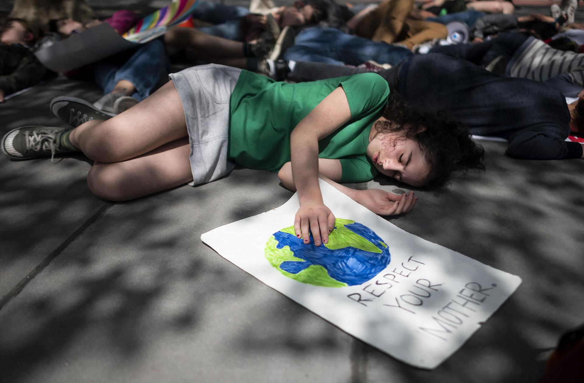 Niños en edad escolar se hacen los muertos durante la Huelga Climática Juvenil el 24 de mayo de 2019 en las afueras de la sede de las Naciones Unidas en la ciudad de Nueva York. (AFP)