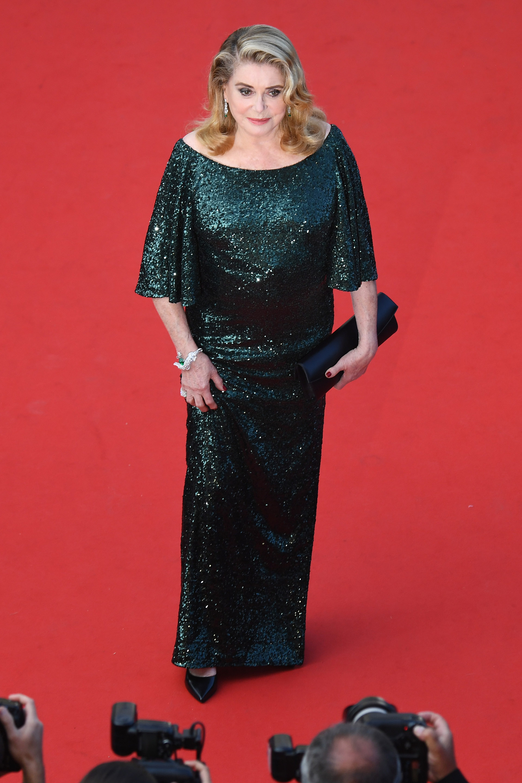 Catherine Deneuve apostó a un vestido de paillettes con escote bote y mangas 3/4 en color verde esmeralda, completando el look con stilettos de cuero negro en punta, clutch a tono y joyas con brillantes y esmeraldas: una esclava y aros gota