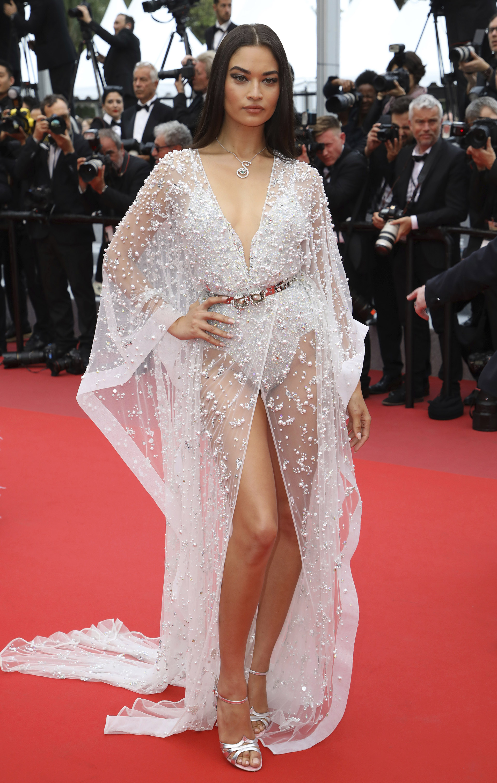 La modelo Shanina Shaik también invitada a Cannes, eligió los brillos y las transparencias. Un body y una túnica bordada con perlas. Completó el look con sandalias plateadas y un collar con forma de ojo con strass y una esmeralda. Su beauty look, un smokey eye en negro y cabello lacio