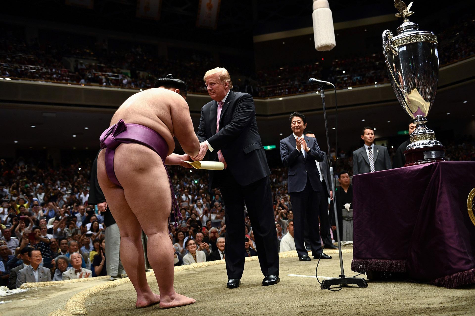 """En medio del """"dohyu"""", al que accedió por una escalerilla especial, Trump leyó un certificado que entregó también a Asanoyama en el que señalaba que ha sido merecedor del trofeo por su """"destacado éxito"""" en el torneo, con 12 victorias y 3 derrotas"""