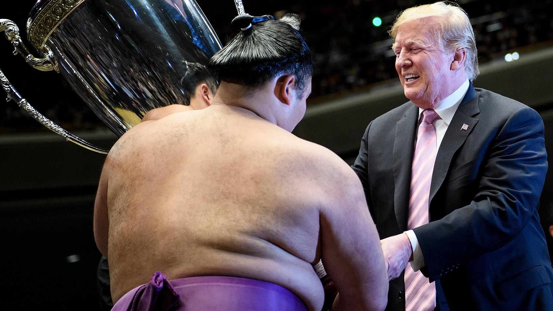 """El luchador ganador, conocido por su nombre deportivo de Asanoyama, recibió el trofeo de parte de Trump, quien tuvo que ser ayudado por el peso de la copa, de unos 30 kilos, que fue entregada en el círculo de arena conocido como """"dohyu"""""""