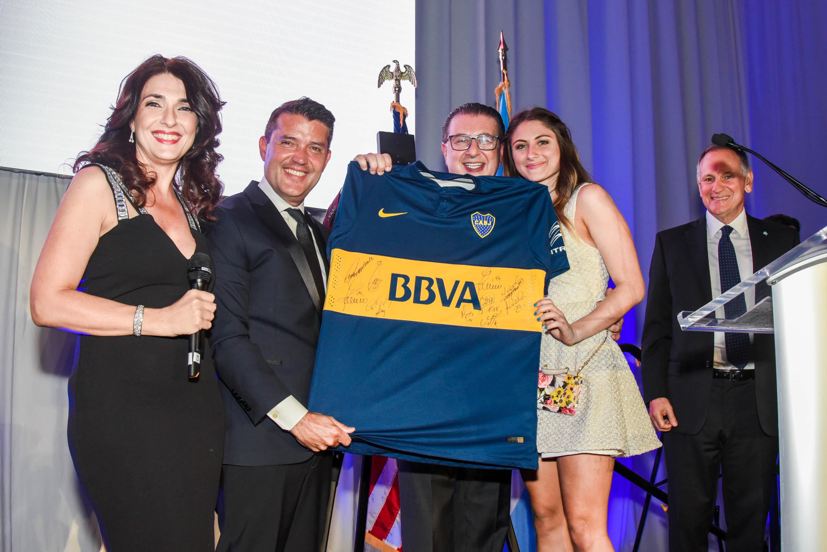 Fátima Slame, presentadora del evento, y Diego Molinari, Vicepresidente 1ro. De la AACC, entregan la camiseta del CABJ a Sergio Codino y su hija