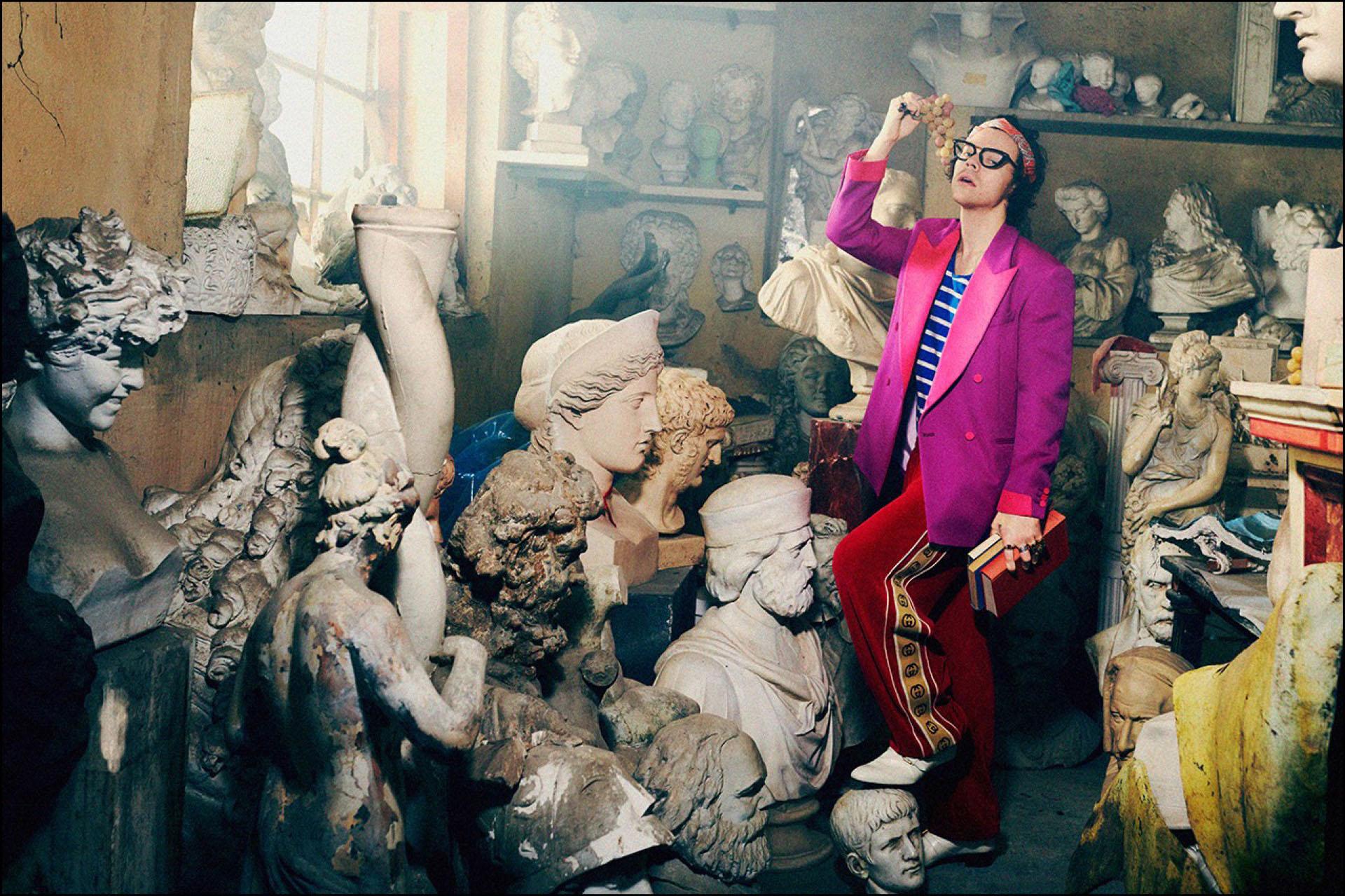 Harry Styles posa con un racimo de uvas entre estatuas y bustos en una mansión florentina para la campaña Pre-Fall 2019 de Gucci Tailoring.