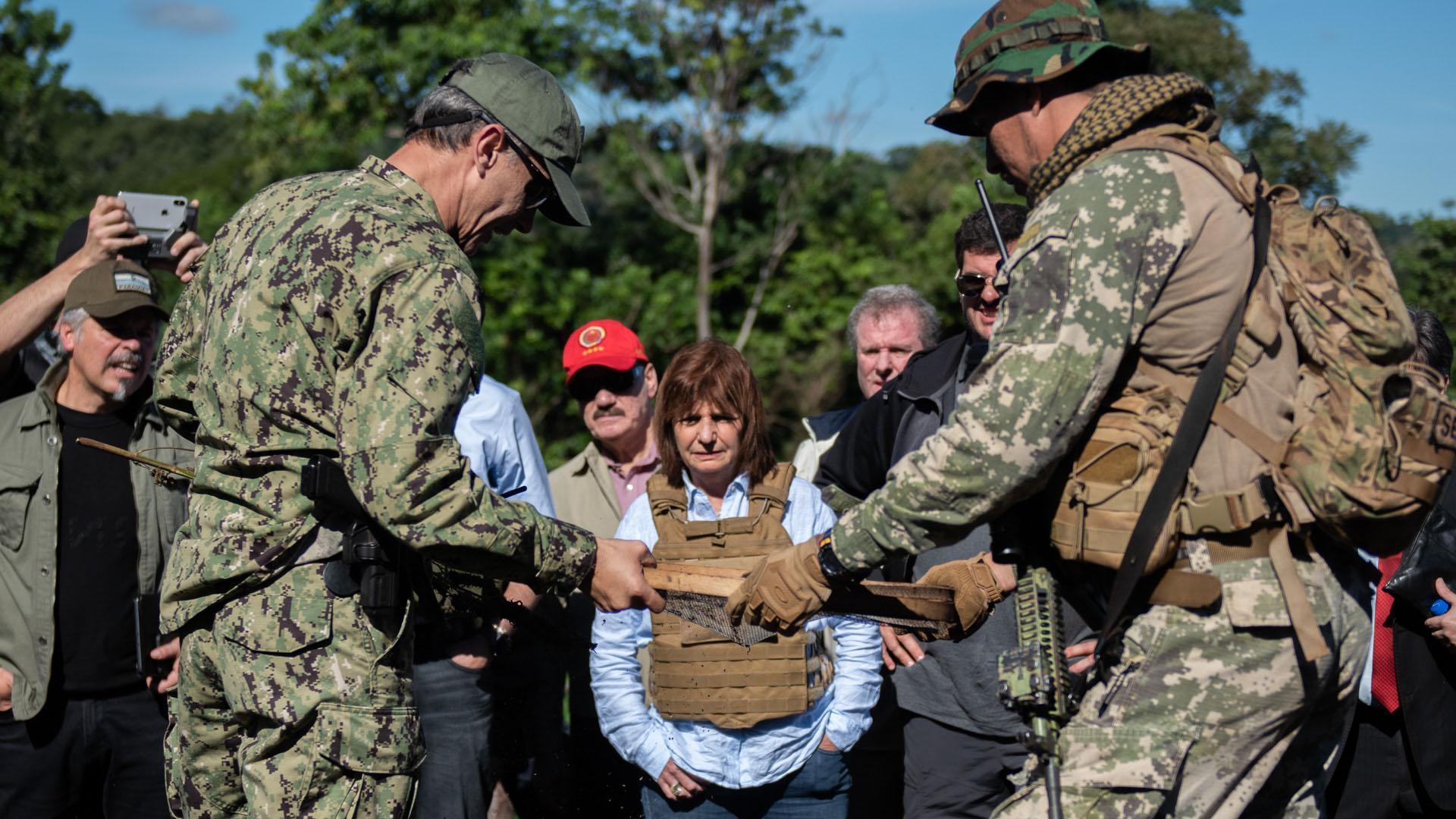 Policías tácticos paraguayos le muestran a Bullrich y a Burzaco el proceso de colado de las plantas ya secas para separar las semillas y las ramas.