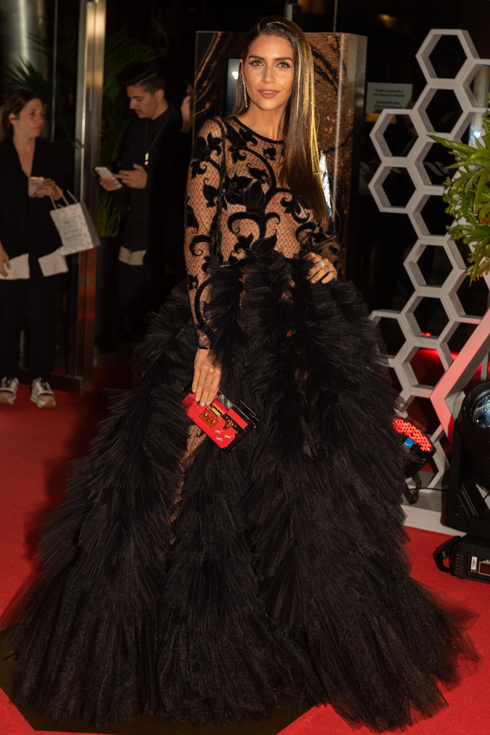 Zaira Nara by Javier Saiach, con vestido negro con transparencias y encaje con terciopelo del mismo tono. Un diseño con escote cerrado y mangas largas con sobrefalda de tul plisado