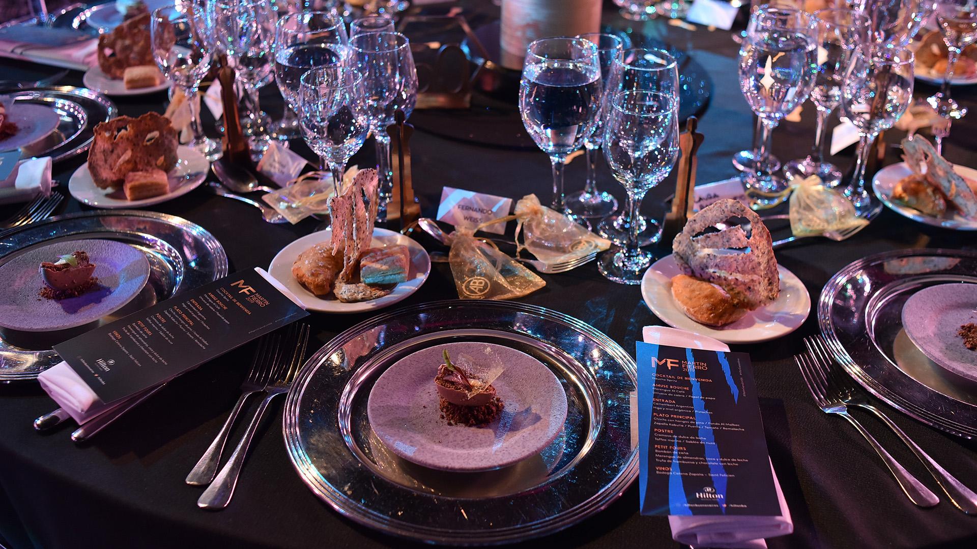 Las lujosas mesas en el salón Pacífico del Hilton. El menú: de entrada, Camembert Argentino con higos, miel orgánica y pistachios; plato principal, chivito con hongos de pino con zapallo kabutia, puerros, tomate y remolacha; de postre, cremoso de dulce de leche, toffee marino y sablée de nuez. Luego, petit fours y café