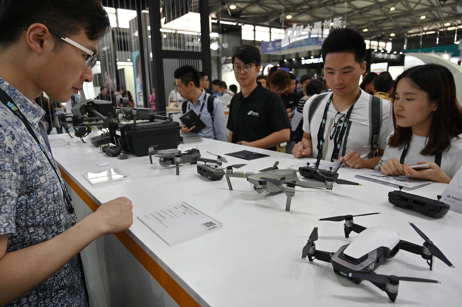 La gente inspecciona los drones DJI durante el Consumer Electronics Show, Ces Asia 2019 en Shanghai el 11 de junio de 2019. (AFP)