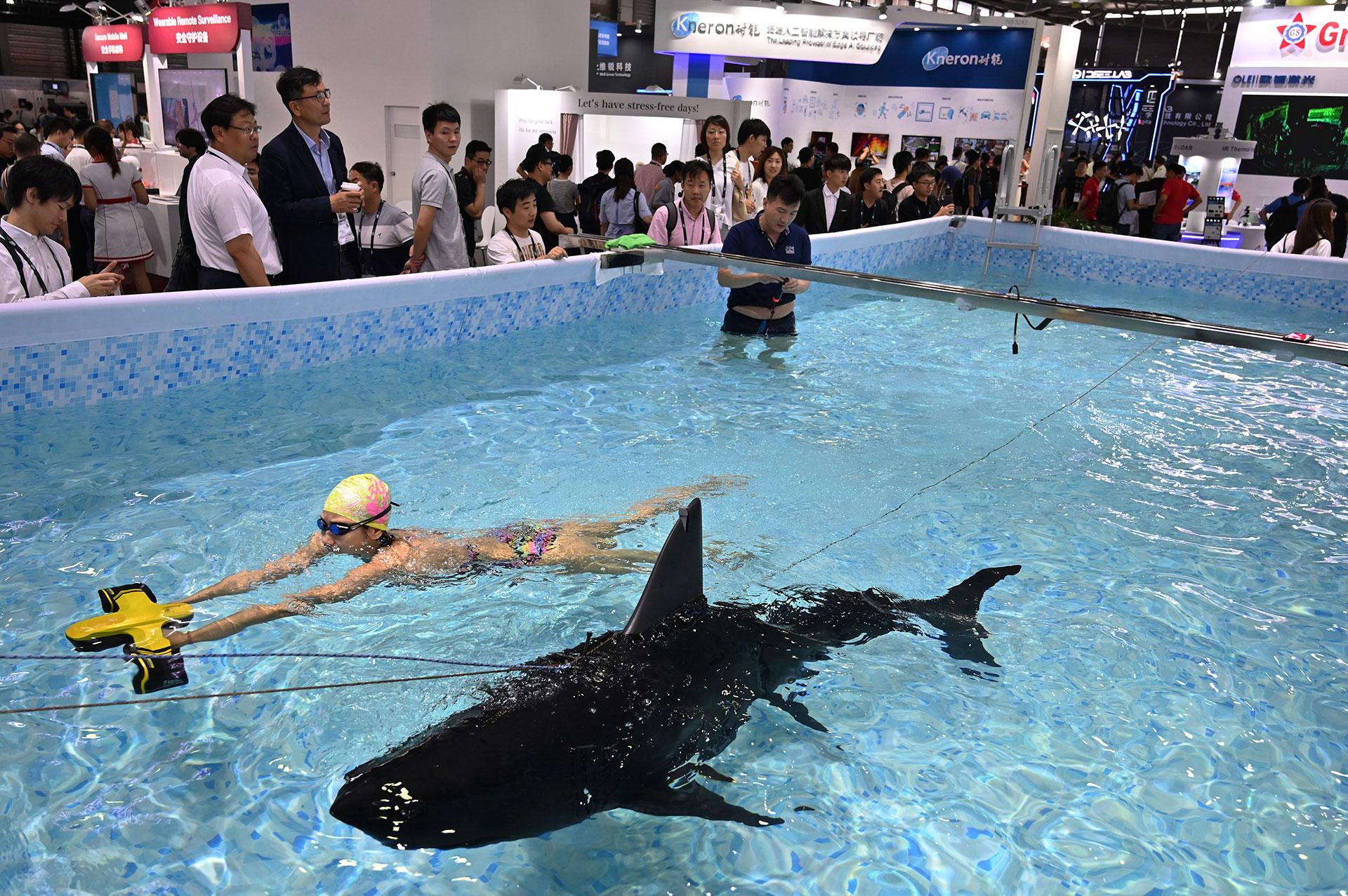 Una mujer nada junto a un robot submarino durante el Consumer Electronics Show, Ces Asia 2019 en Shanghai el 11 de junio de 2019. (AFP)