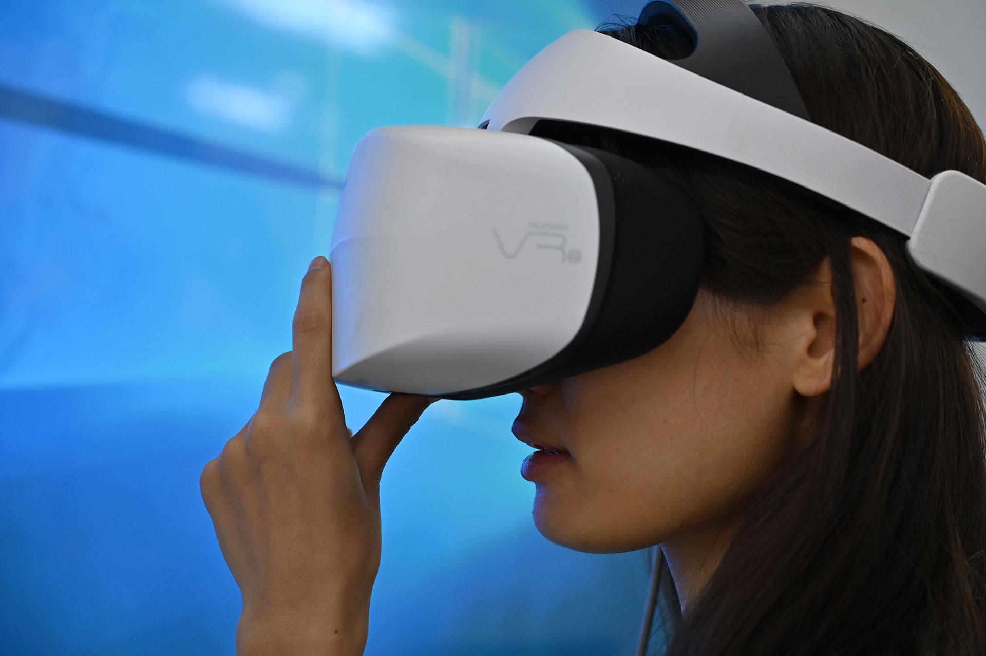 Una mujer prueba unos lentes de realidad virtual 3D durante el Consumer Electronics Show en Shanghai el 11 de junio de 2019. (AFP)