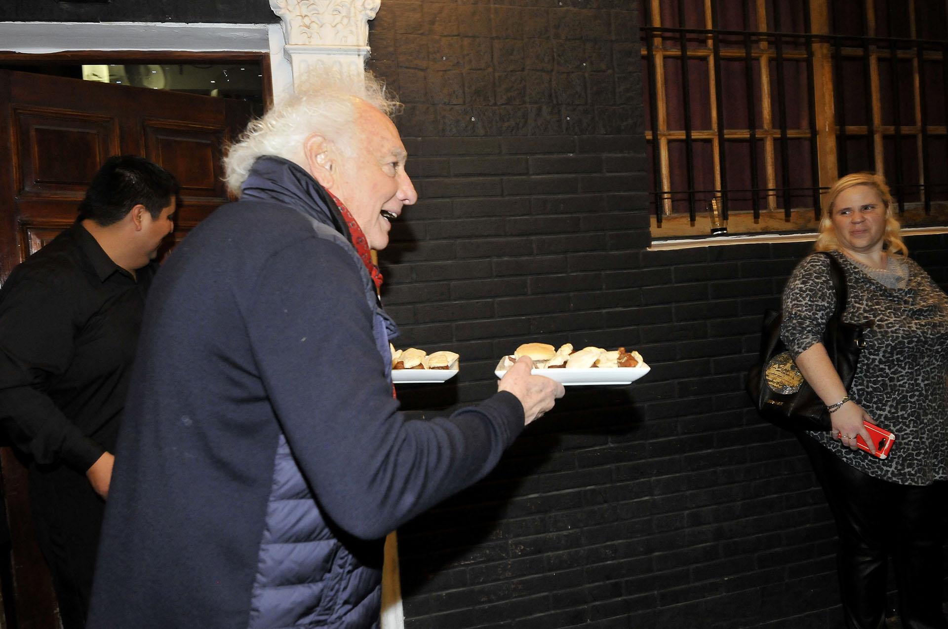 Guillermo Coppola llevando comida a los invitados
