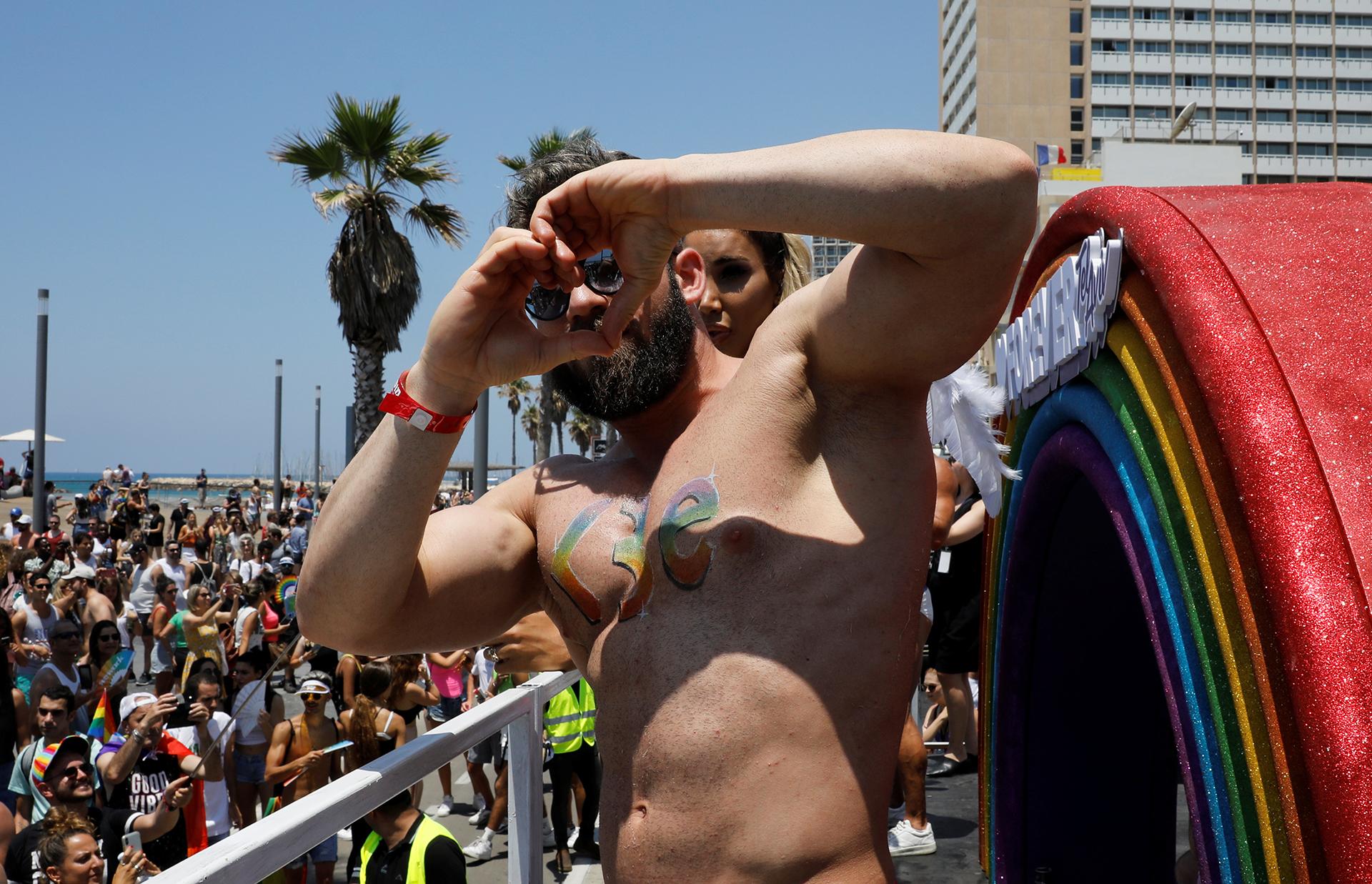 Un hombre forma un corazón con sus manos en el desfile gay de Tel Aviv
