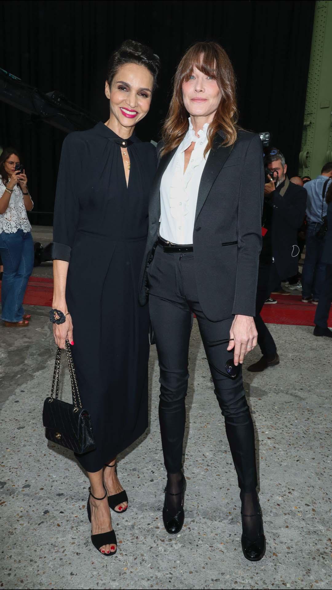 Carla Bruni lució un look muy casual con un traje de sastre negro y camisa blanca con volantes en el centro que combinó con unas merceditas con tacón. En la foto posó con la modelo francesa Farida Khelfa