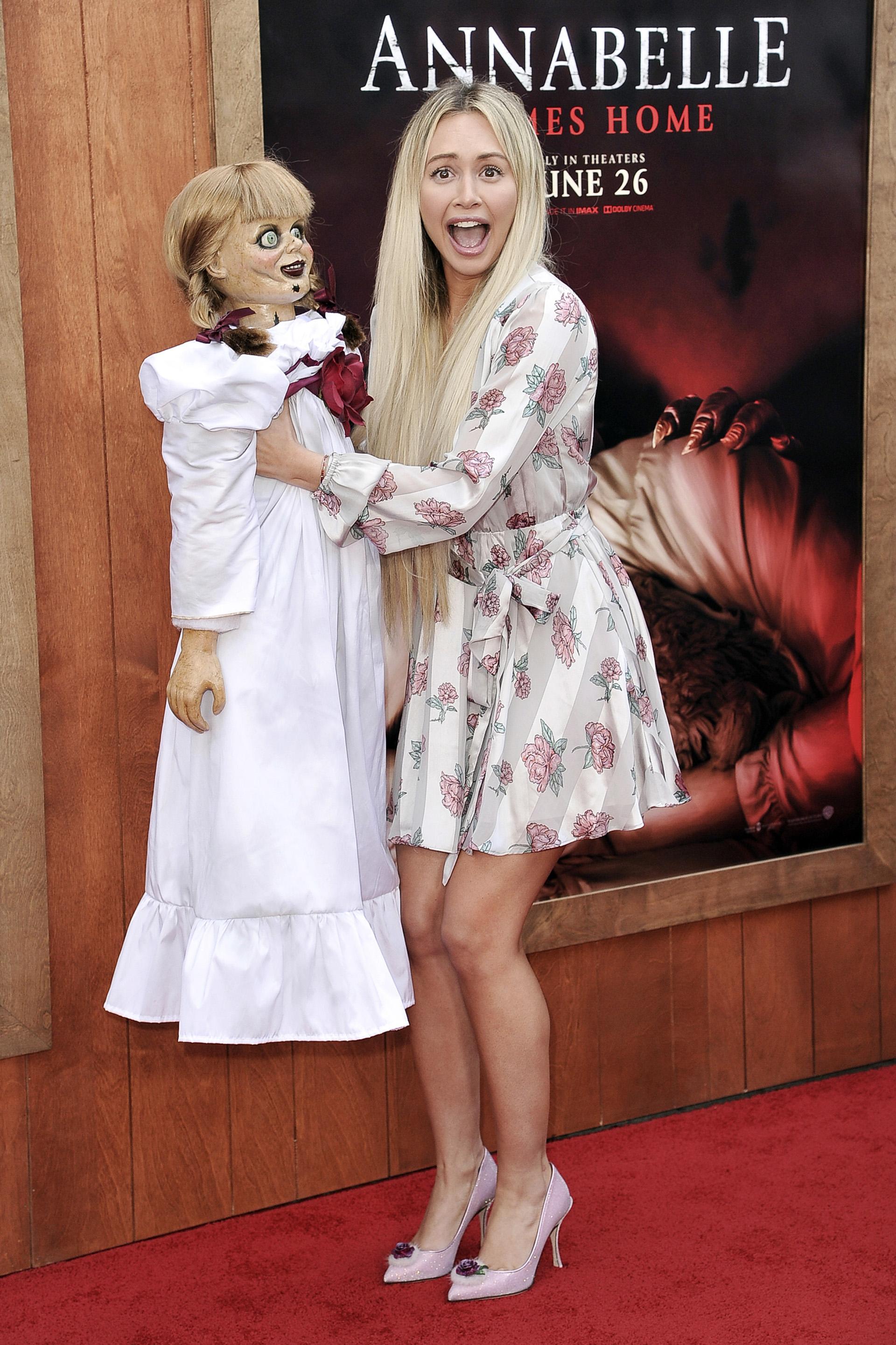 Corinne Olympios junto a la temible Annabelle. Los demonólogos Ed y Lorraine Warren se llevan a la muñeca poseída a su casa y la guardan bajo llave. Pero una noche, Annabelle despierta y se pone como objetivo matar a la hija pequeña y a las amigas de los Warren