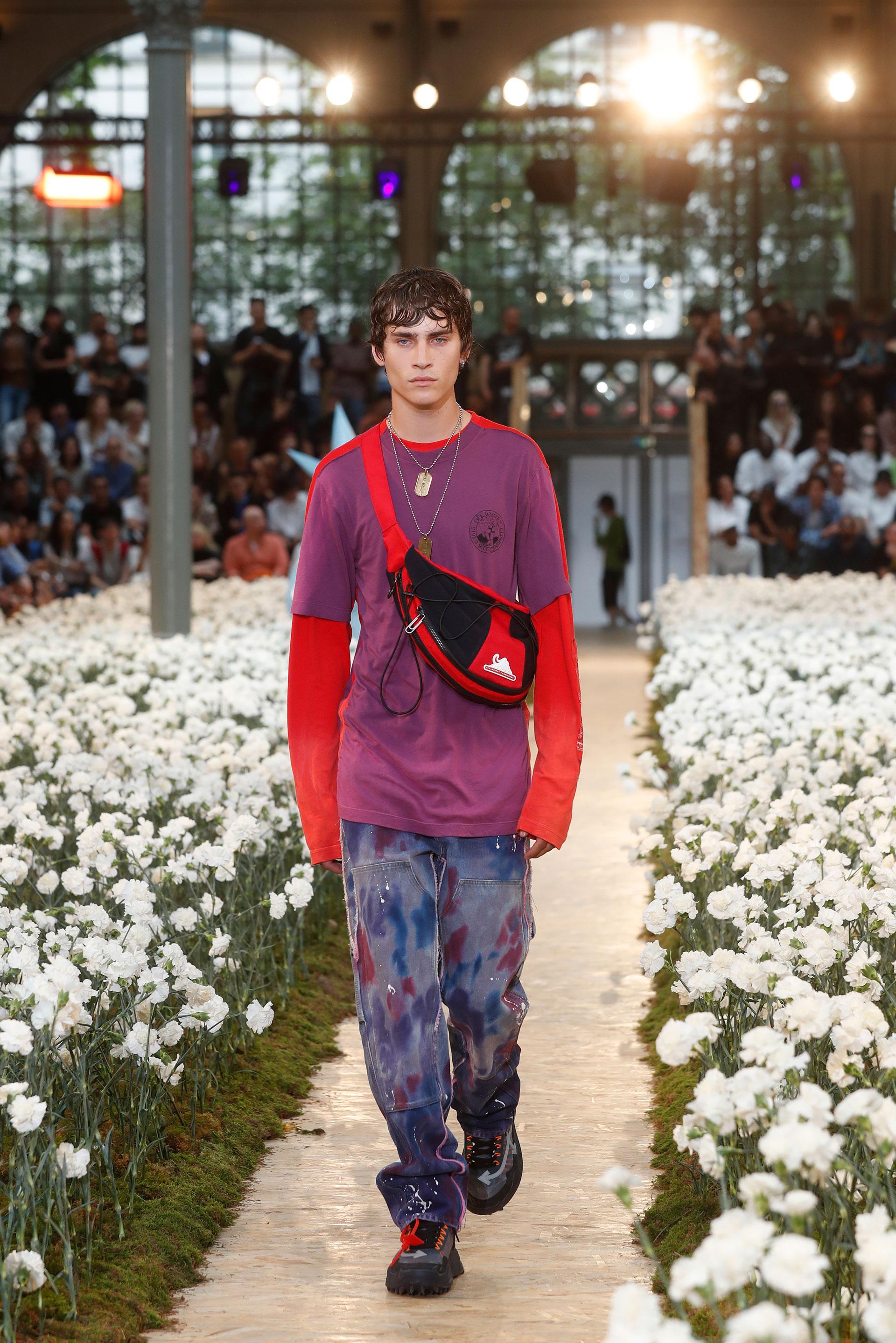 Relajado y entrecasa. De mangas largas, una remera de algodón en púrpura y rojo combinada con pantalones cargo pintados. Los accesorios fashionistas, una riñonera, las ugly shoes de hombres y collares con chapas