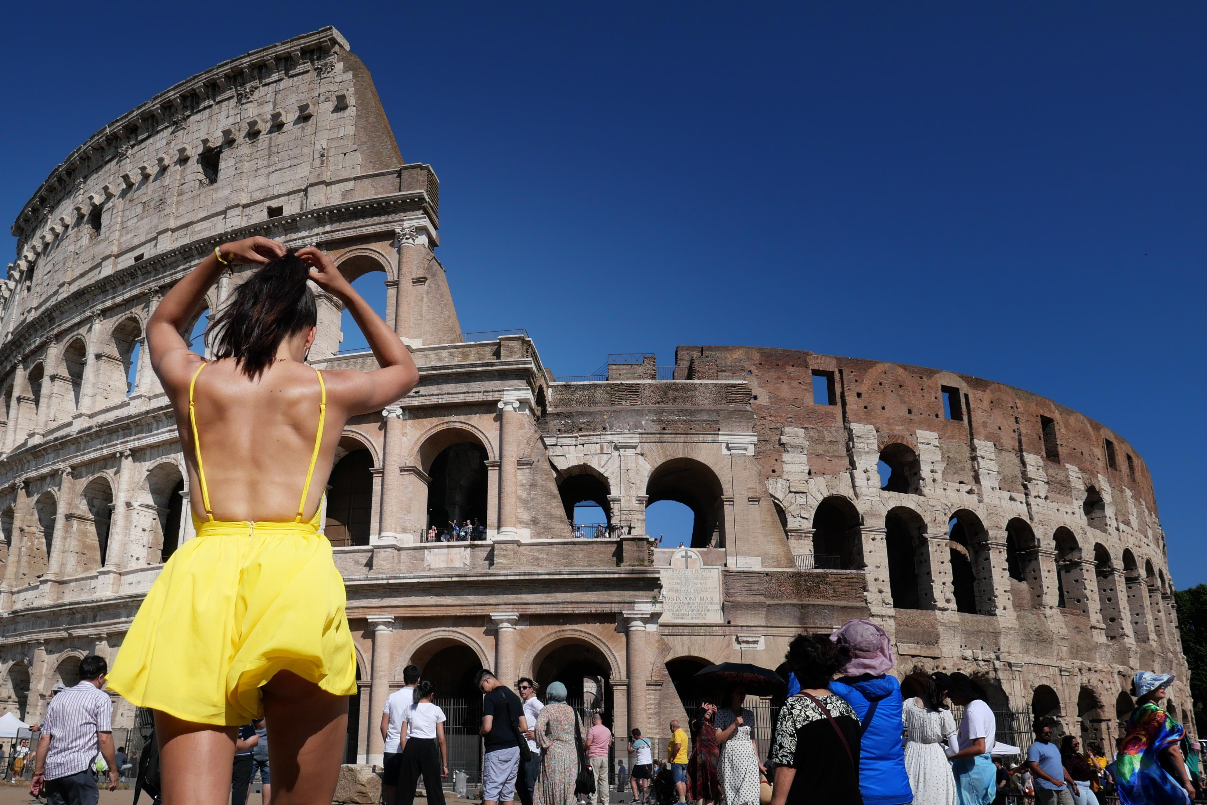 Una turista ajusta su cabello mientras camina bajo el sol frente al Coliseo, en Roma (Alberto Pizzoli/ AFP)
