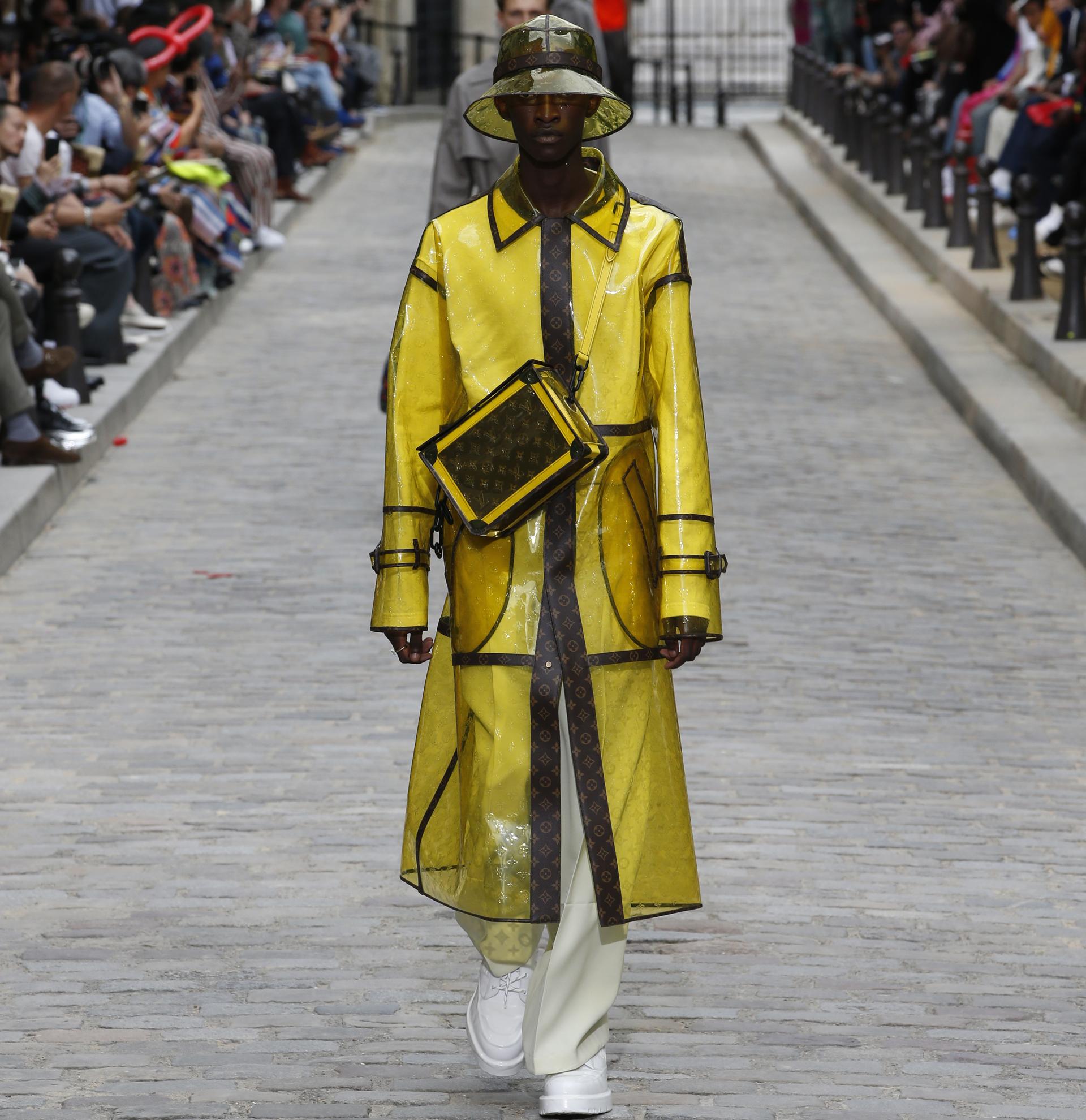 Uno de los protagonistas de la colección de Louis Vuitton fue el impermeable con el logotipo de la marca. De corte midi y con el sombrero haciendo juego, el look lo completó una crossbody en amarillo con el monogram en marrón