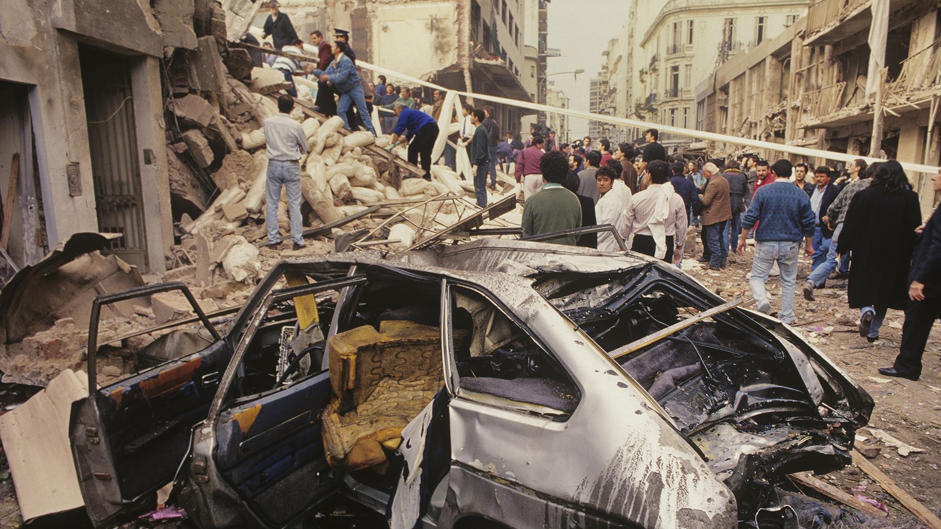 """La explosión traducida en los escombros, las fachadas de enfrente a la AMIA y el auto. El fotógrafo explicó: """"Esta imagen da un poco de magnitud del atentado. Fue una fotografía muy usada por los medios porque el primer plano del coche destruido genera muchas lecturas"""" (Julio Menajovsky)"""