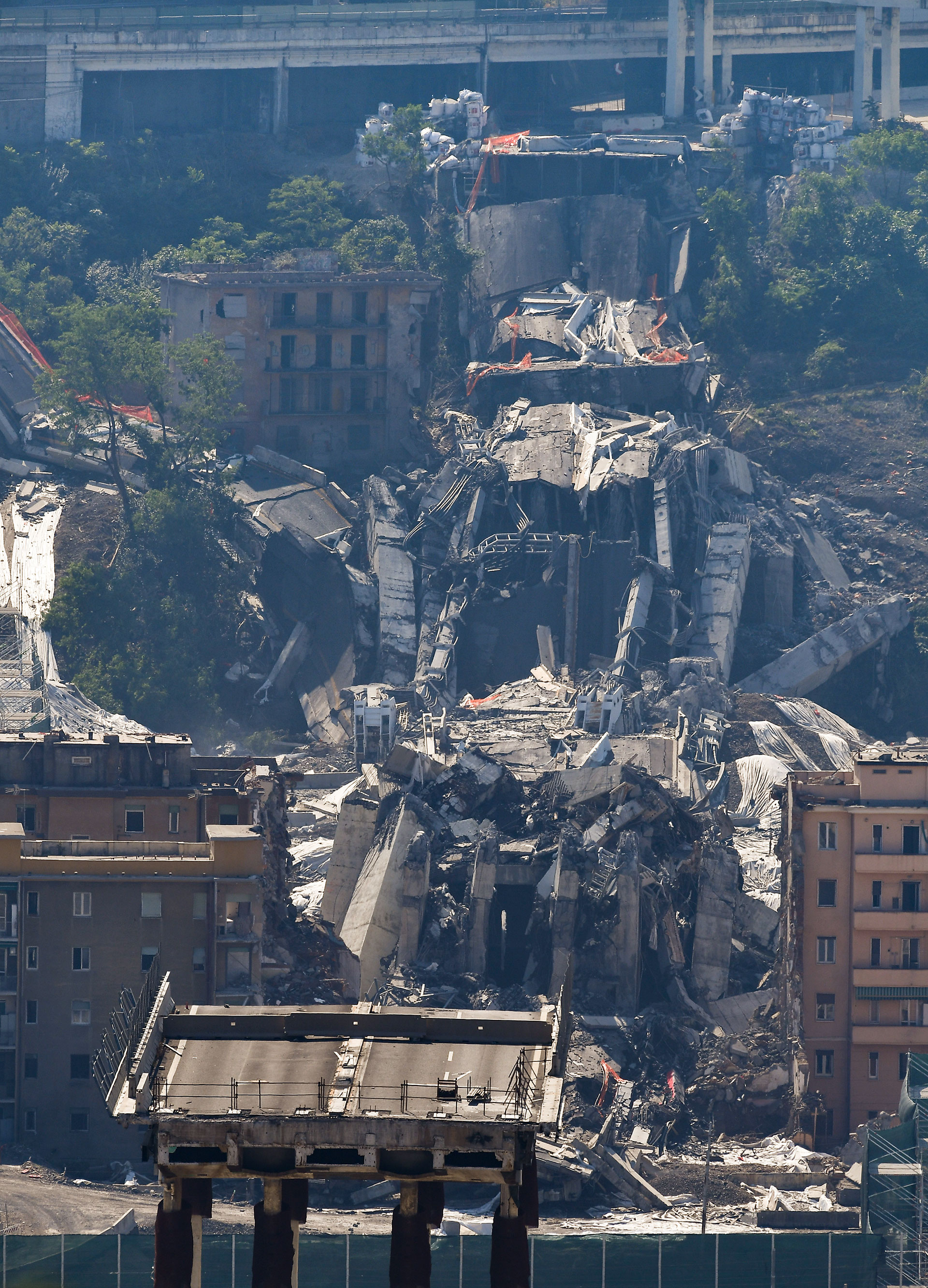 El tablero del puente, entre los escombros y los edificios evacuados después de que cargas explosivas volaran los pilones (AFP)