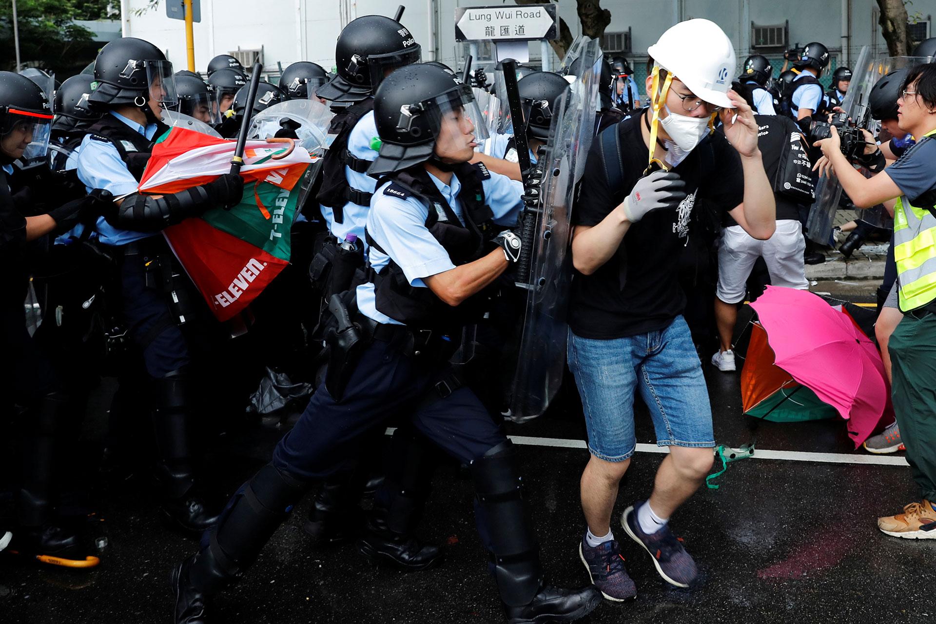 La policía intenta dispersar a los manifestantes cerca de una ceremonia de bandera. (Reuters / Tyrone Siu)