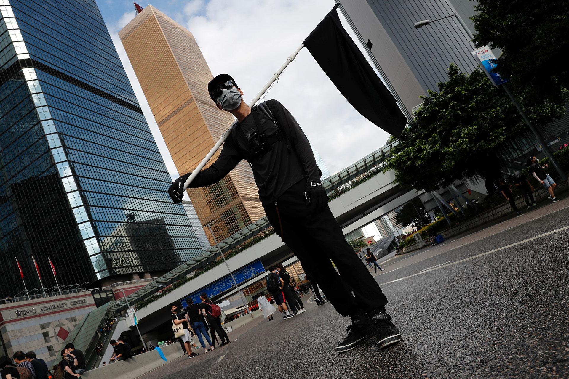 Un manifestante en contra de la extradición lleva una bandera negra. (Reuters / Tyrone Siu)
