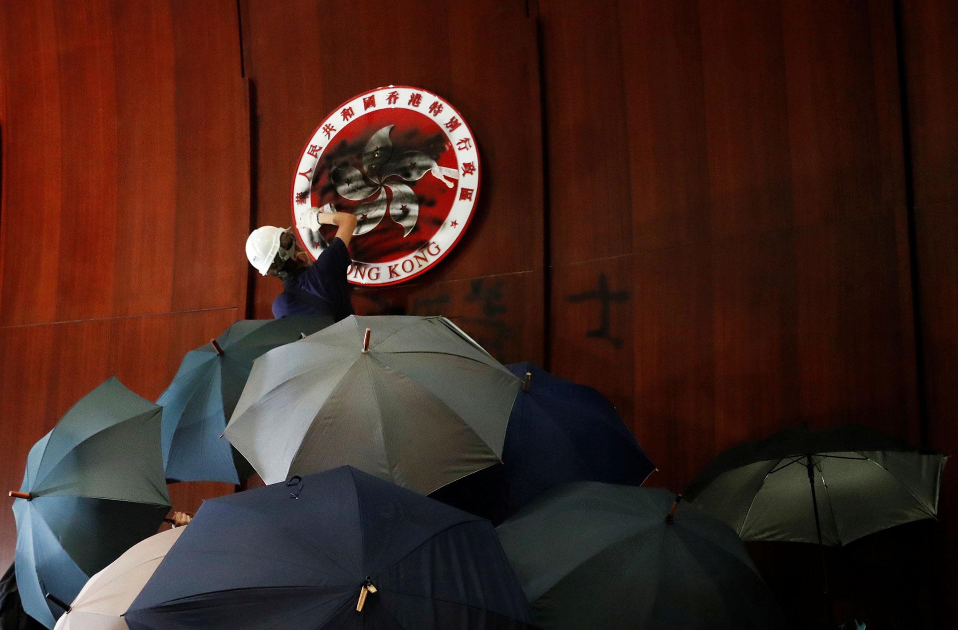 Una persona rocía pintura sobre los escudos de armas de Hong Kong dentro de una cámara legislativa. (Reuters / Tyrone Siu)
