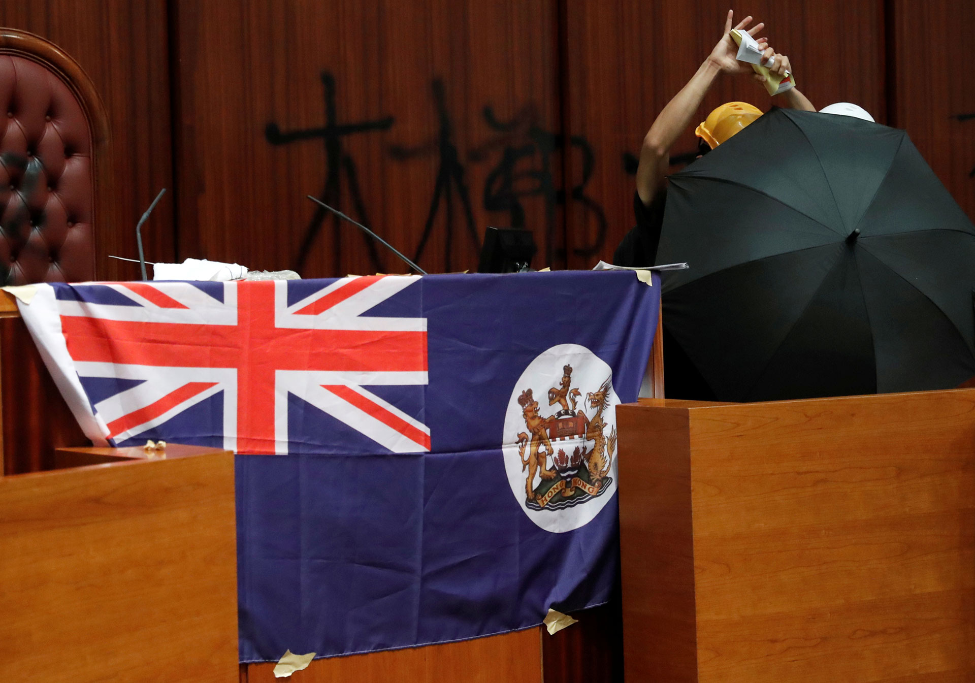 Una persona rasga un libro de la Ley Básica de Hong Kong mientras está al lado de una bandera colonial del país desplegada dentro de la cámara legislativa. (Reuters/ Tyrone Siu)