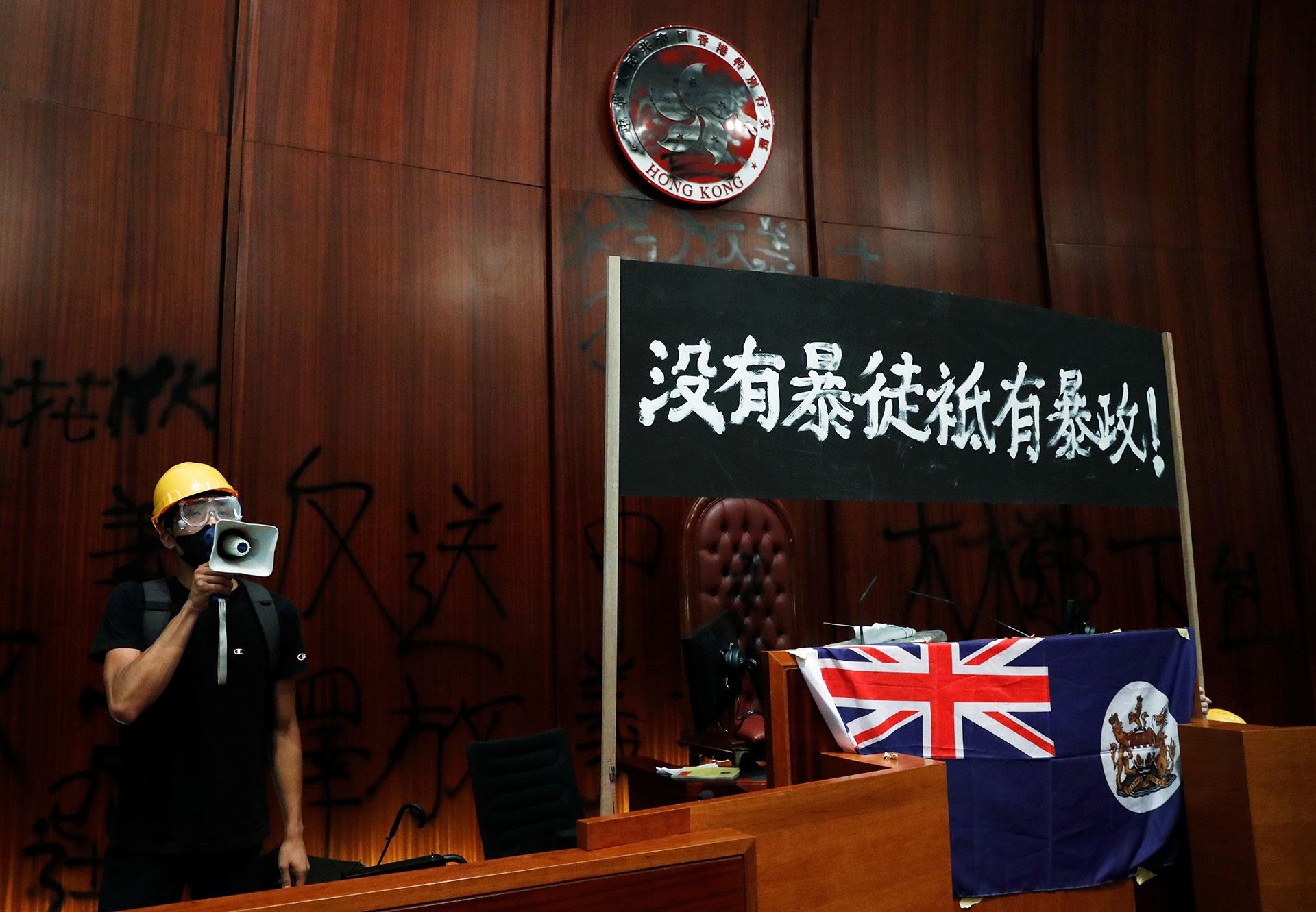 """Un manifestante habla dentro del Consejo Legislativo junto a la bandera de la era colonial británica y un cartel que reza: """"No hay vándalos, hay una tiranía"""". (Reuters)"""