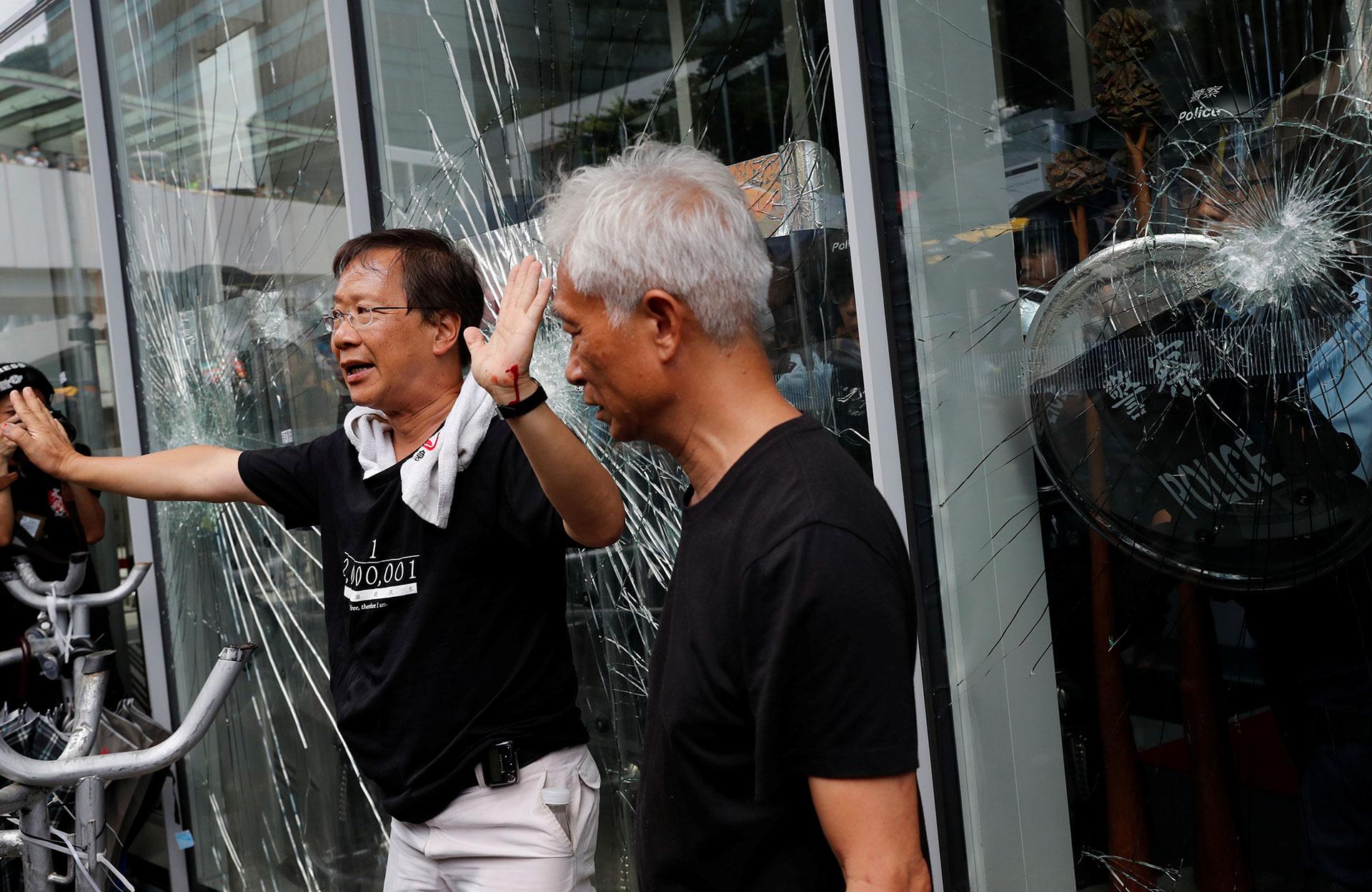Los legisladores Kwok Ka-ki y Leung Yiu-chung intentan calmar a los manifestantes mientras estos intentan ingresar al edificio del Consejo Legislativo (Reuters / Tyrone Siu)
