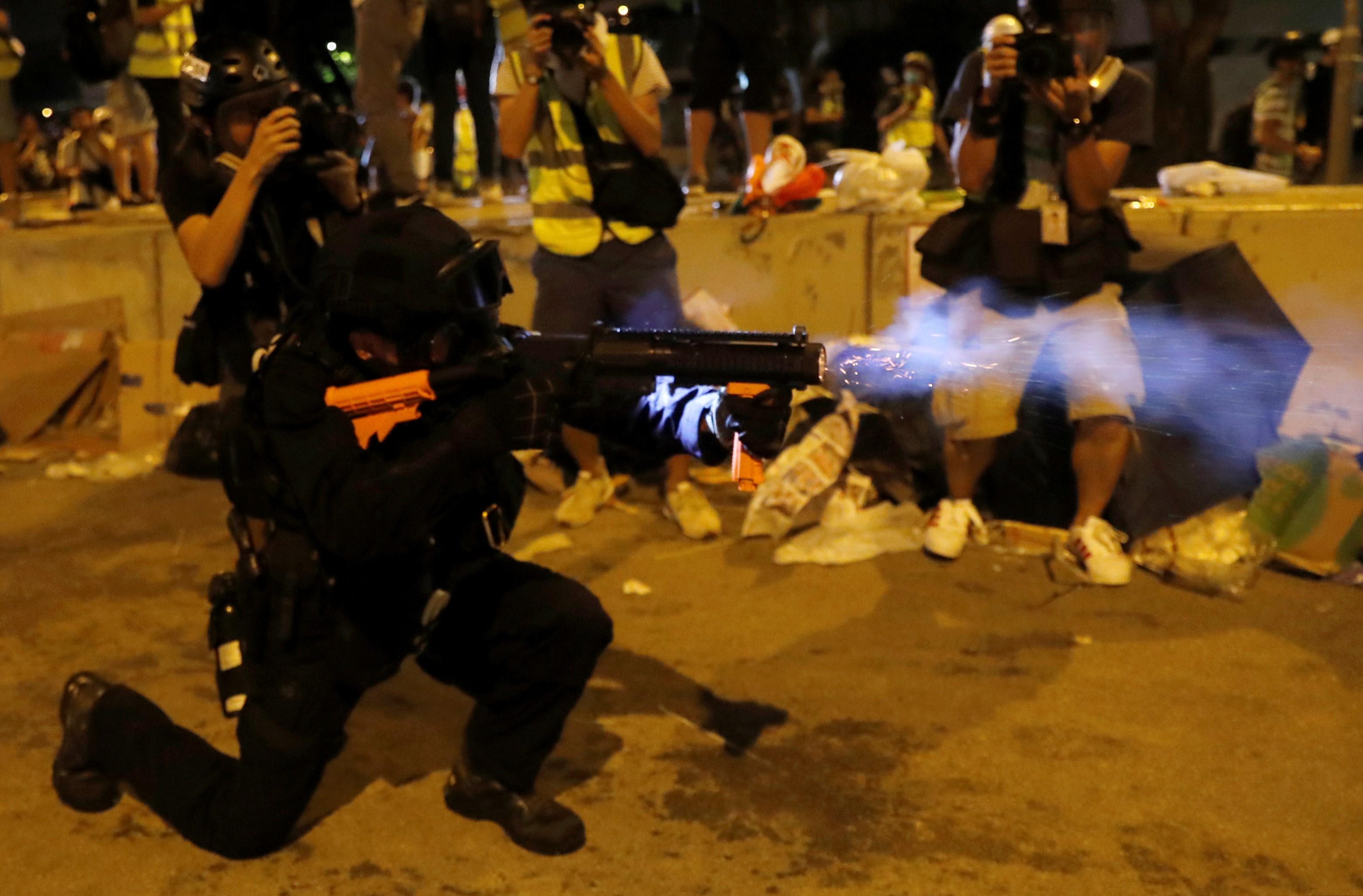 Un agente de la Policía lanza una granada de gas lacrimógeno en las adyacencias del edificio de la Legislatura para dispersar a los manifestantes