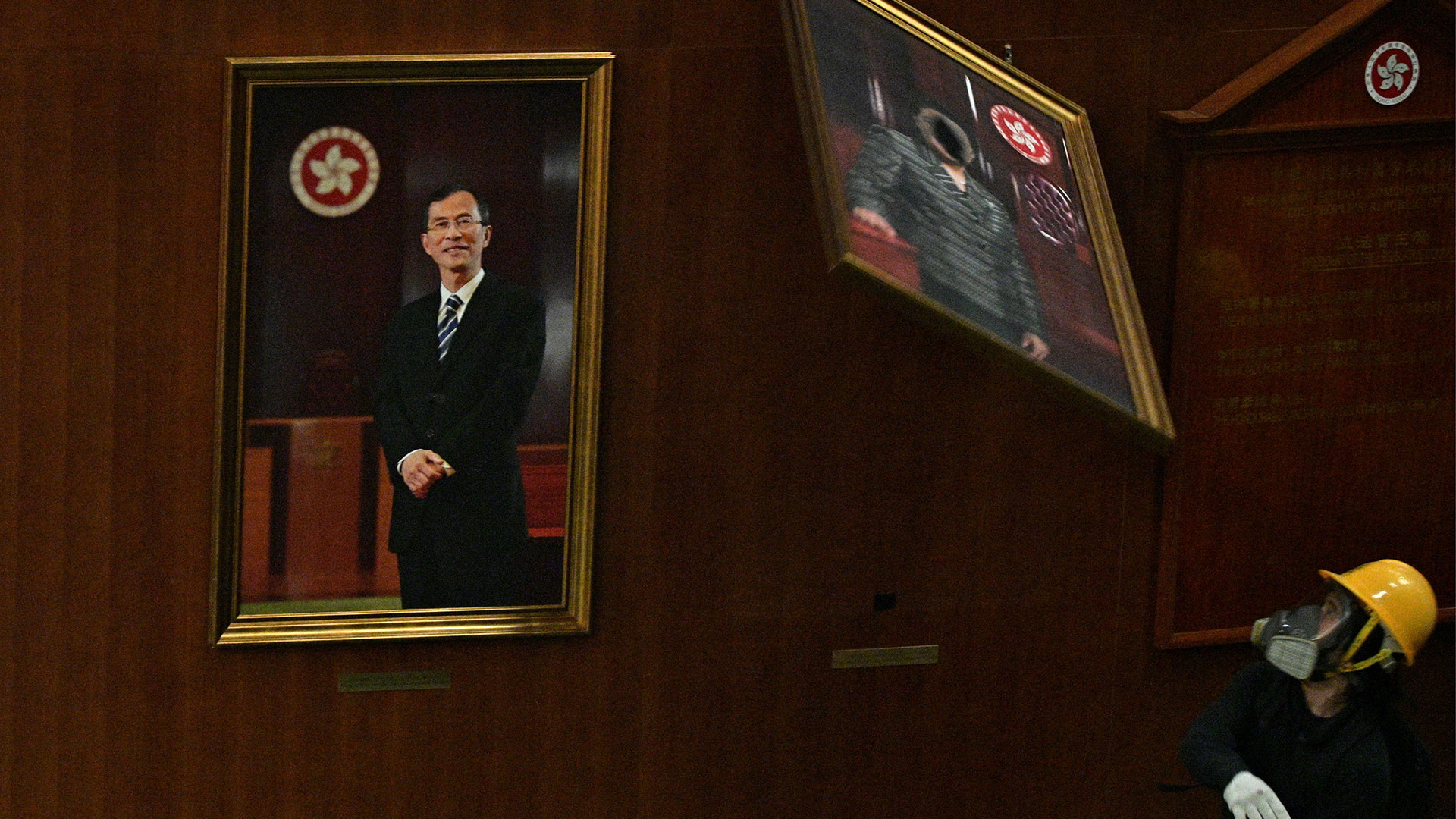 Un manifestante arroja el retrato de un político que estaba colgado dentro del recintolegislativo