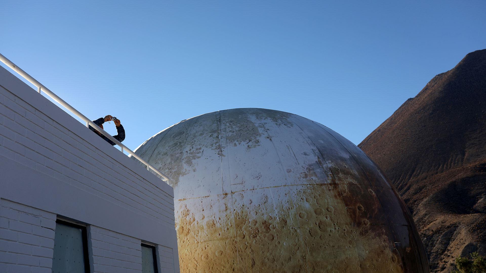 Un visitante toma fotografías desde una terraza en el Observatorio Mamalluca (Reuters)
