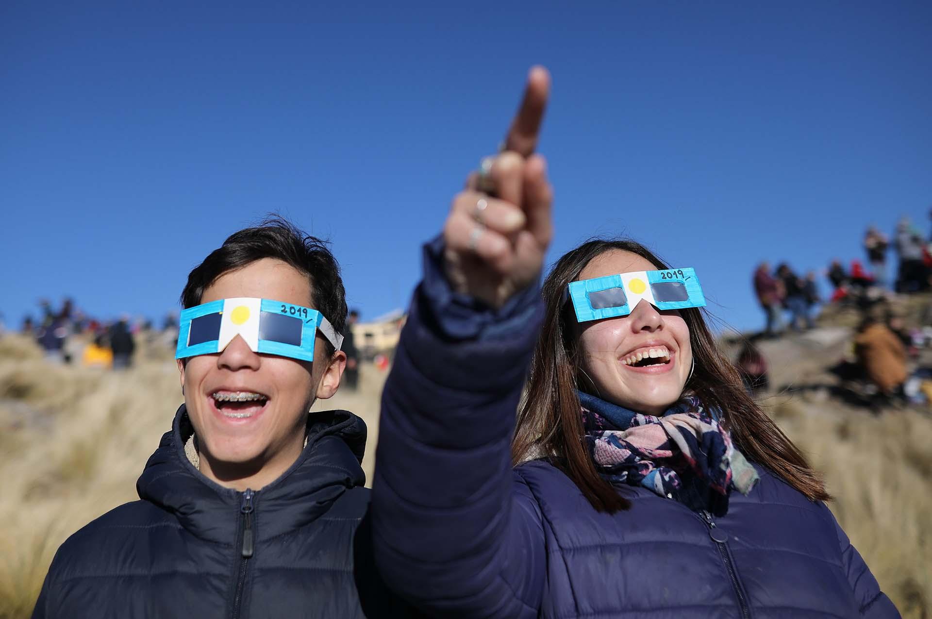 Dos niños con anteojos protectores miran el sol antes del eclipse solar total en Merlo, Argentina (EFE/Nicolas Aguilera)