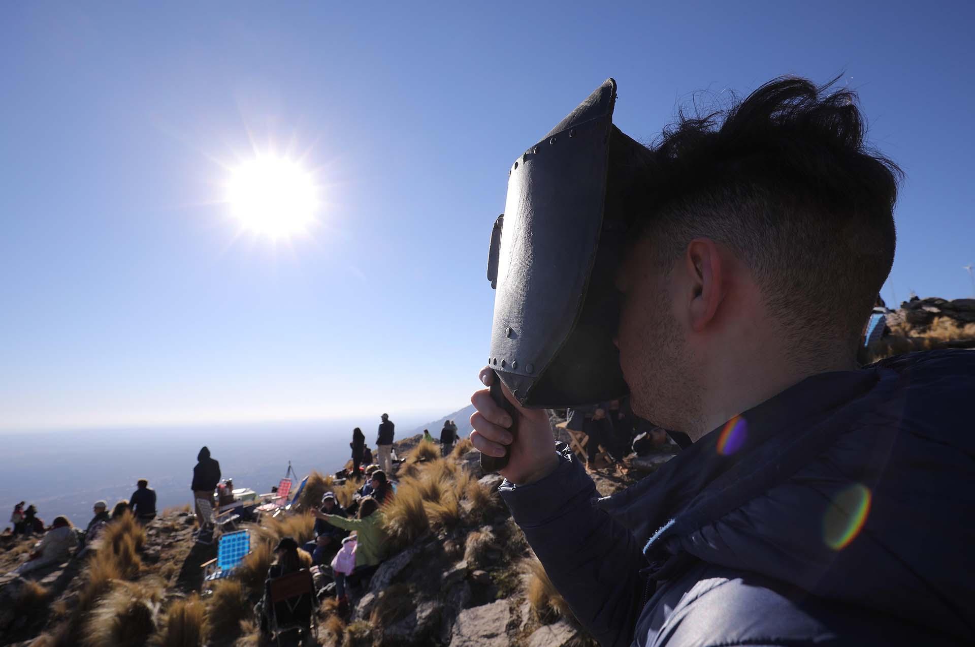 Un hombre mira el sol con una mascara para soldar antes del eclipse solar total en la ciudad de Merlo, San Luis, Argentina (EFE/Nicolas Aguilera)