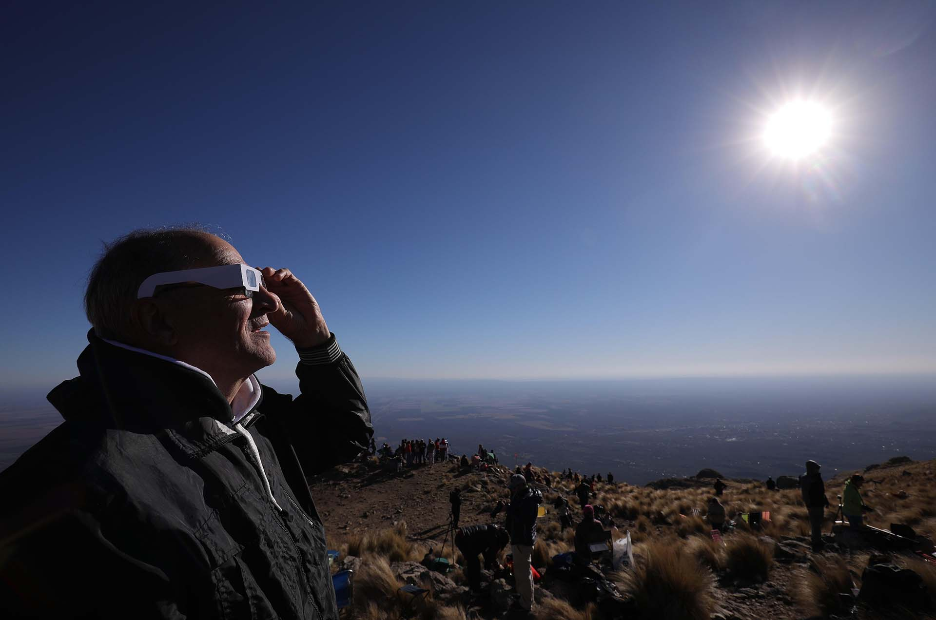 Un hombre mira el sol con anteojos especiales antes del eclipse solar total este martes en la ciudad de Merlo, San Luis, Argentina (EFE/Nicolas Aguilera)
