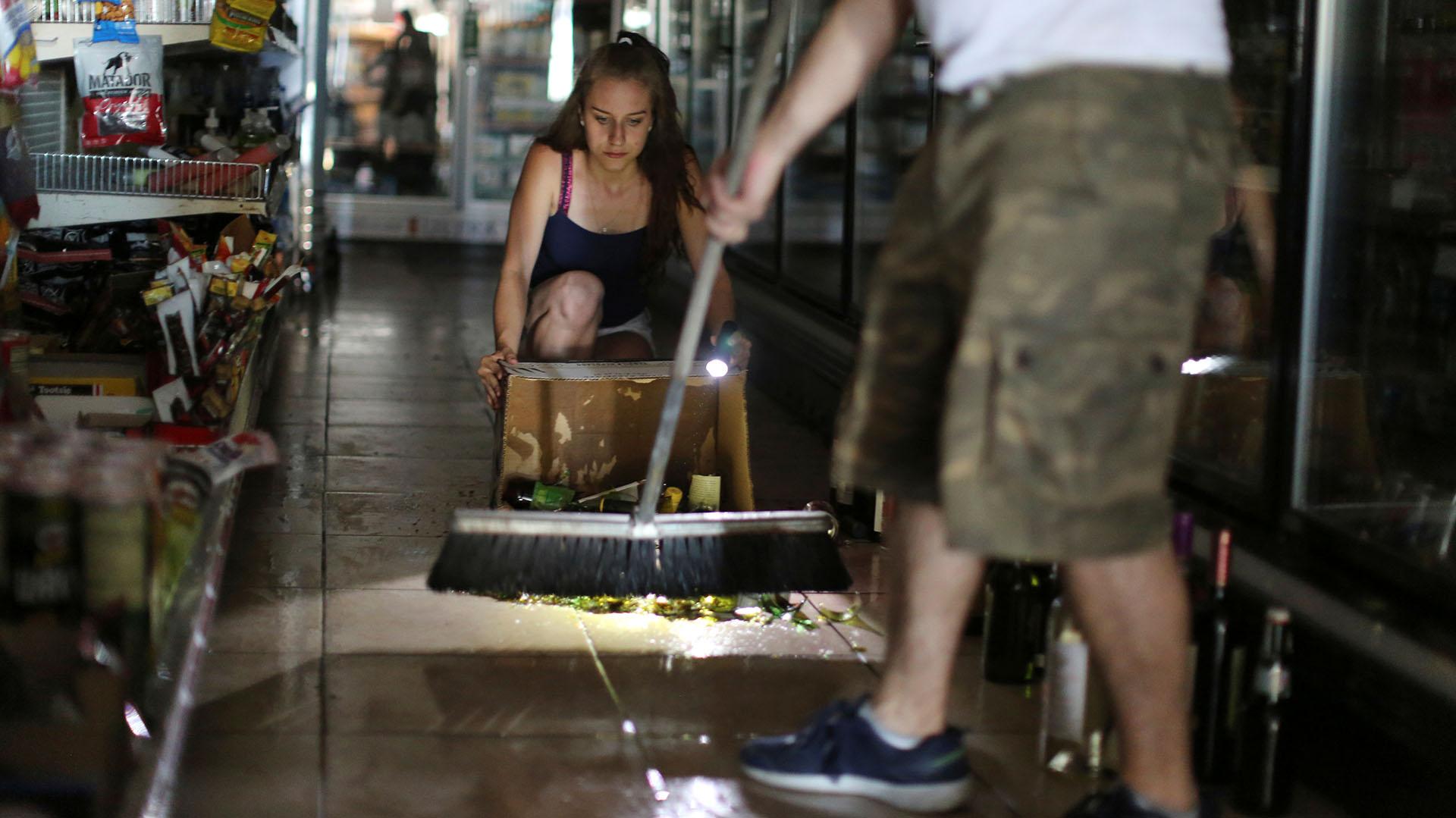 Dos personas limpian los destrozos por los terremotos (REUTERS/David McNew)
